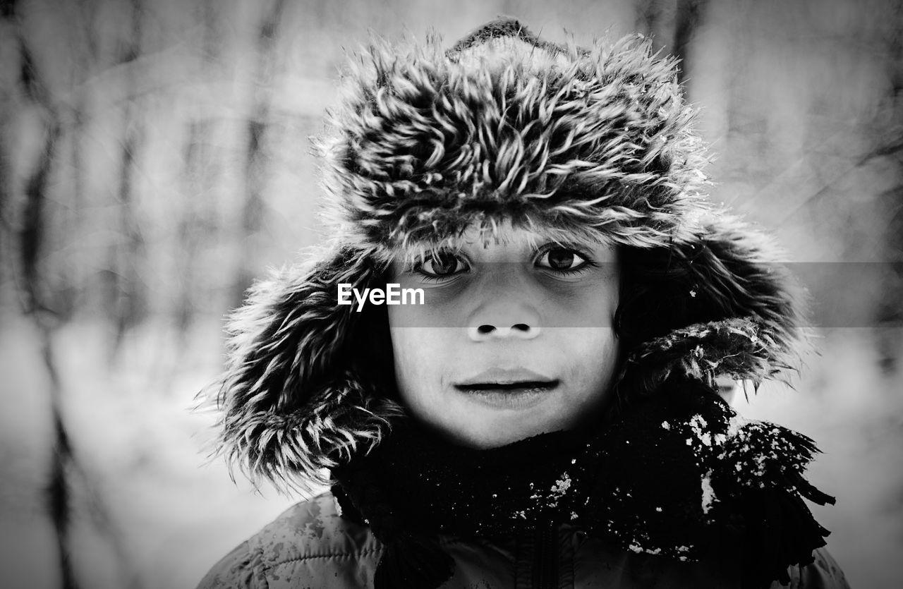Close-Up Portrait Of Boy Wearing Fur Hat