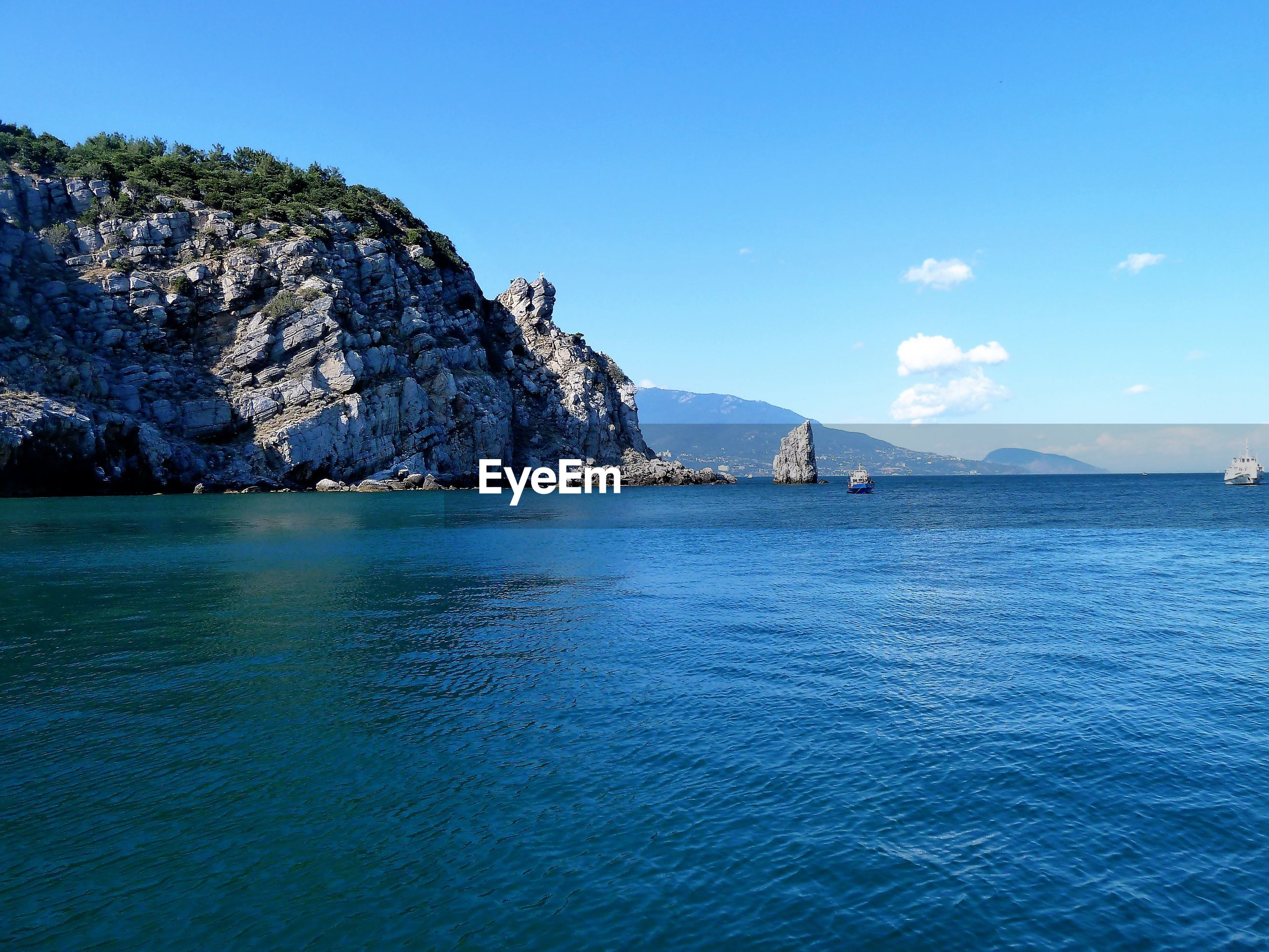 SCENIC VIEW OF SEA AND ROCKS AGAINST BLUE SKY