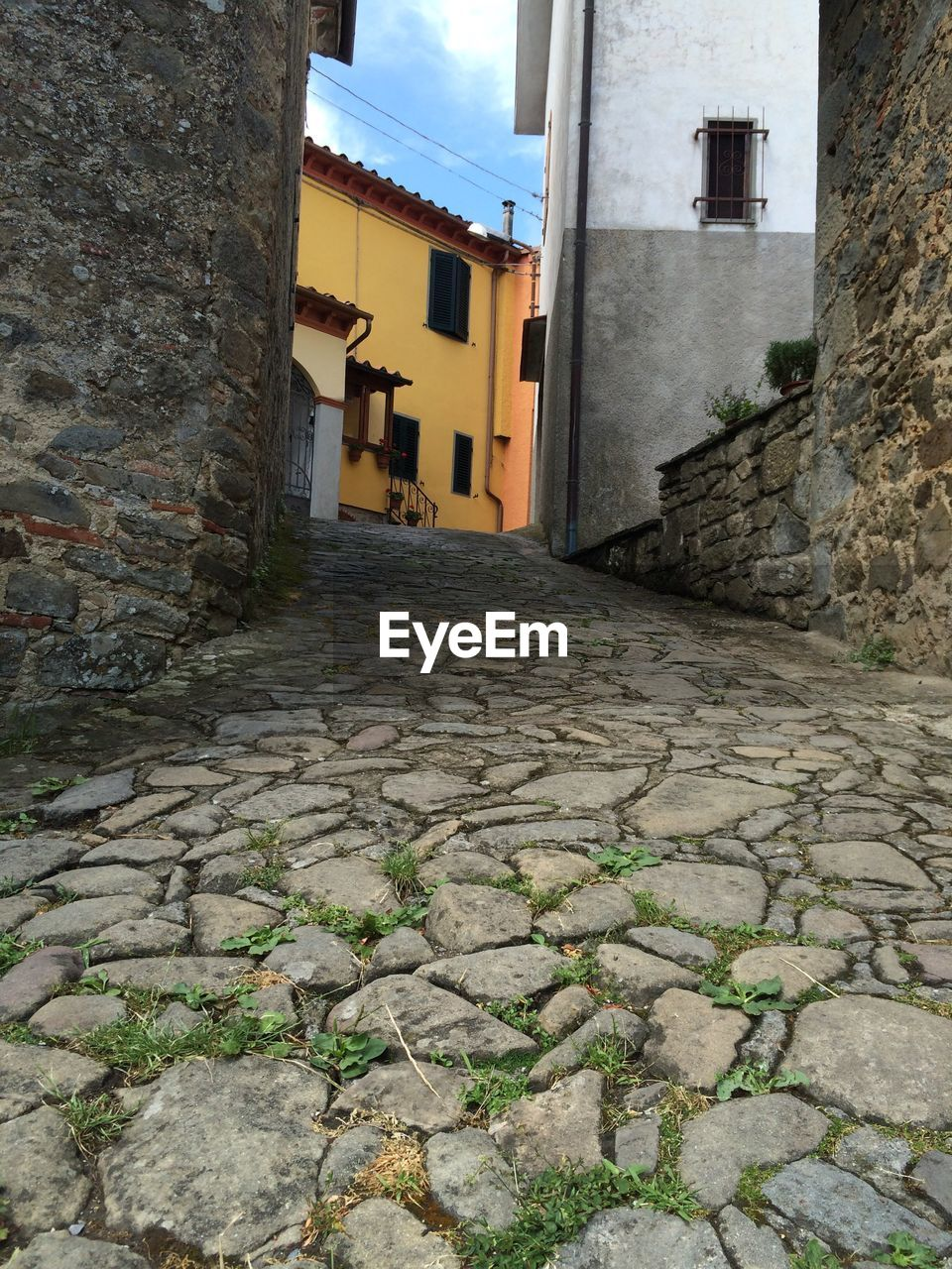 architecture, built structure, building exterior, building, the way forward, direction, city, footpath, cobblestone, residential district, no people, house, day, street, wall, outdoors, narrow, stone wall, nature, wall - building feature, alley, paving stone