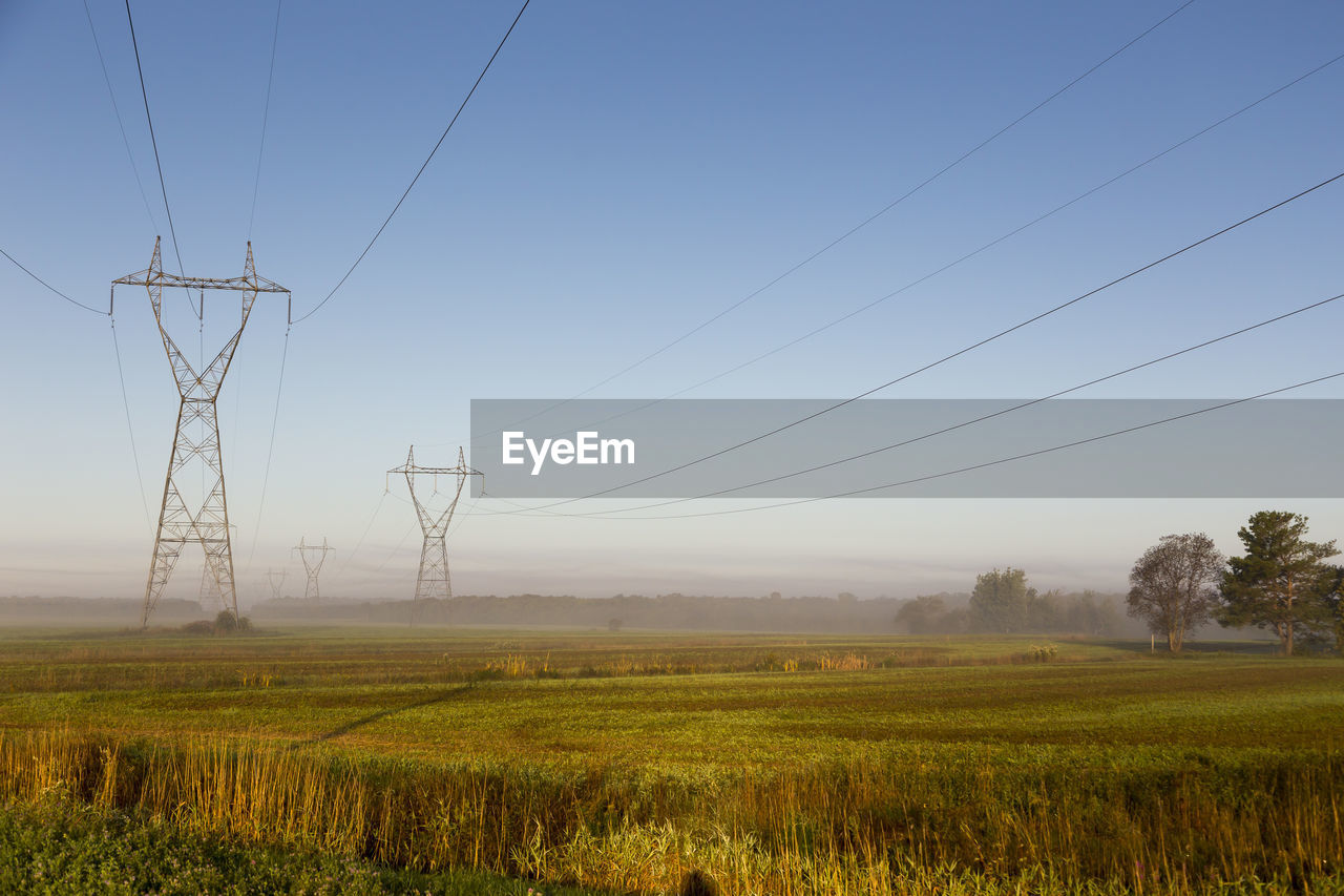 landscape, sky, field, cable, environment, land, power line, electricity, technology, electricity pylon, tranquility, tranquil scene, beauty in nature, power supply, plant, scenics - nature, rural scene, nature, connection, fog, no people, outdoors