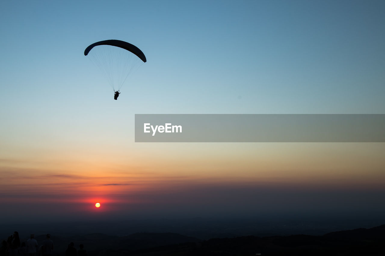 Low Angle View Of Silhouette Paragliding Against Clear Sky