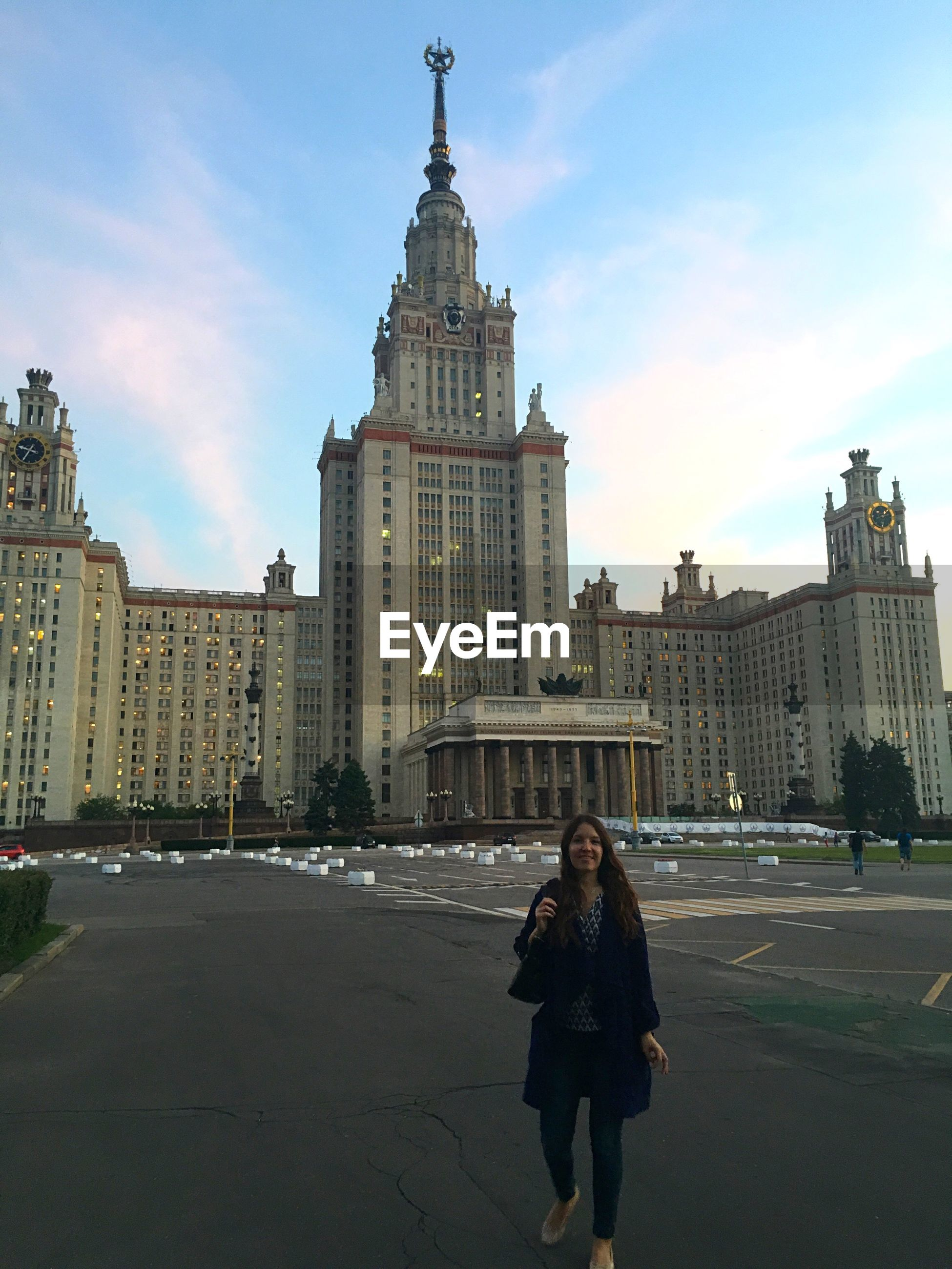 Smiling woman standing on street against lomonosov moscow state university
