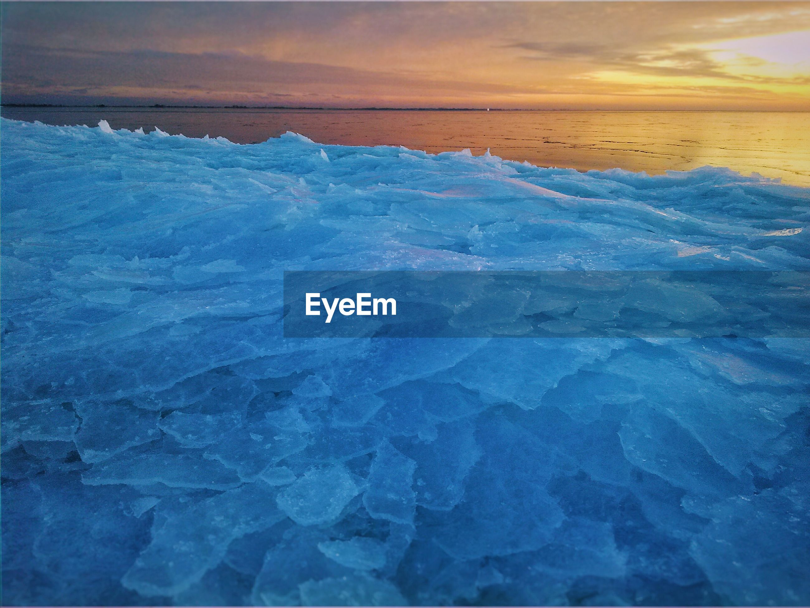Ice crystals by sea during sunset