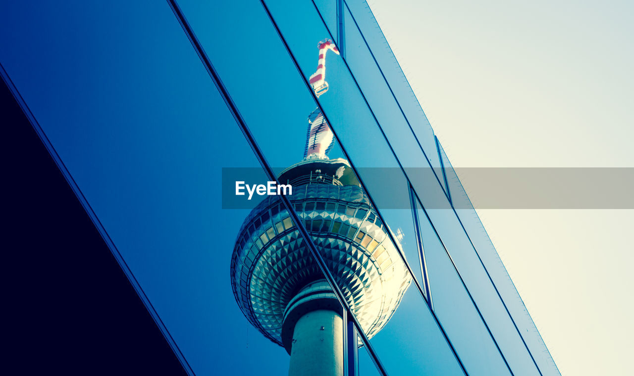Reflection Of Television Tower In Modern Building Against Blue Sky