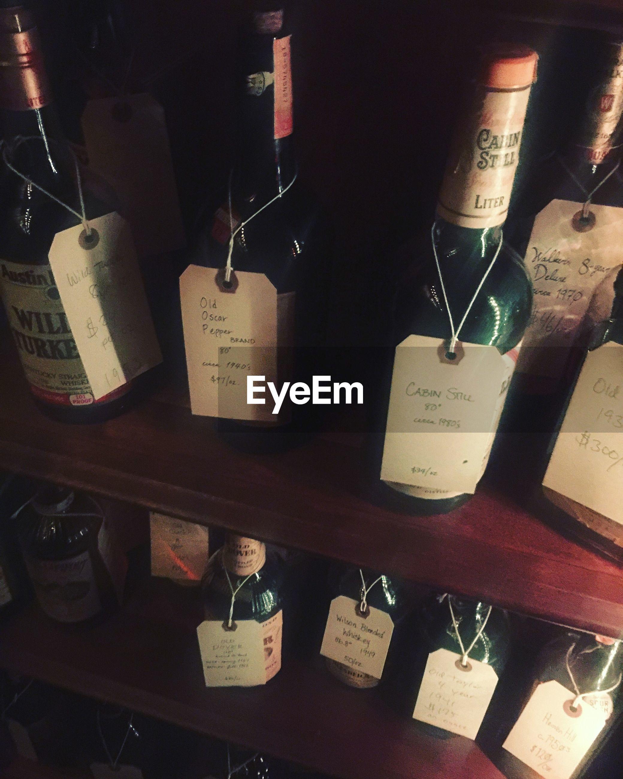 CLOSE-UP OF WINE BOTTLES HANGING IN SHELF