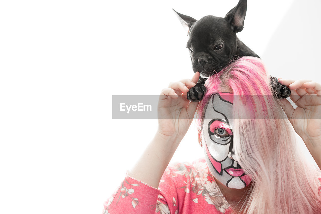 Close-Up Portrait Of Woman With Face Paint Holding Puppy Against White Background