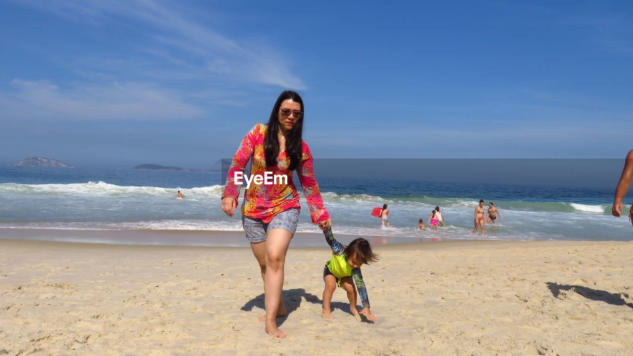 Mother holding hands of son while walking on sand against sea