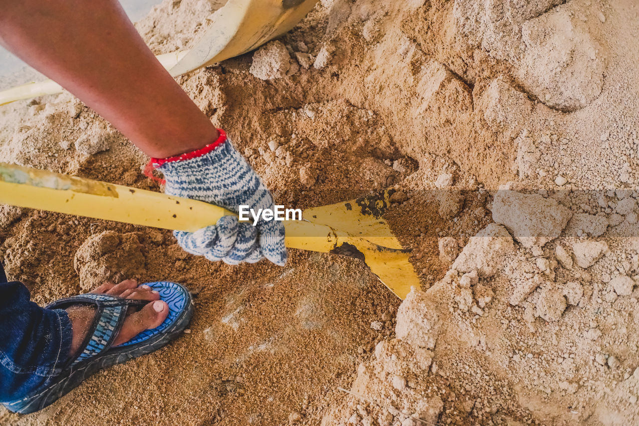 low section, one person, human body part, human leg, lifestyles, real people, body part, land, nature, day, standing, leisure activity, shoe, dirt, outdoors, human hand, high angle view, yellow, women, hand, mud, finger