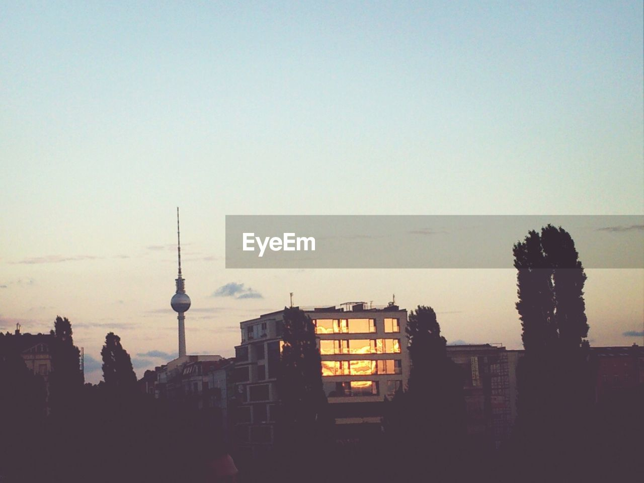 Building and fernsehturm against sky during sunset
