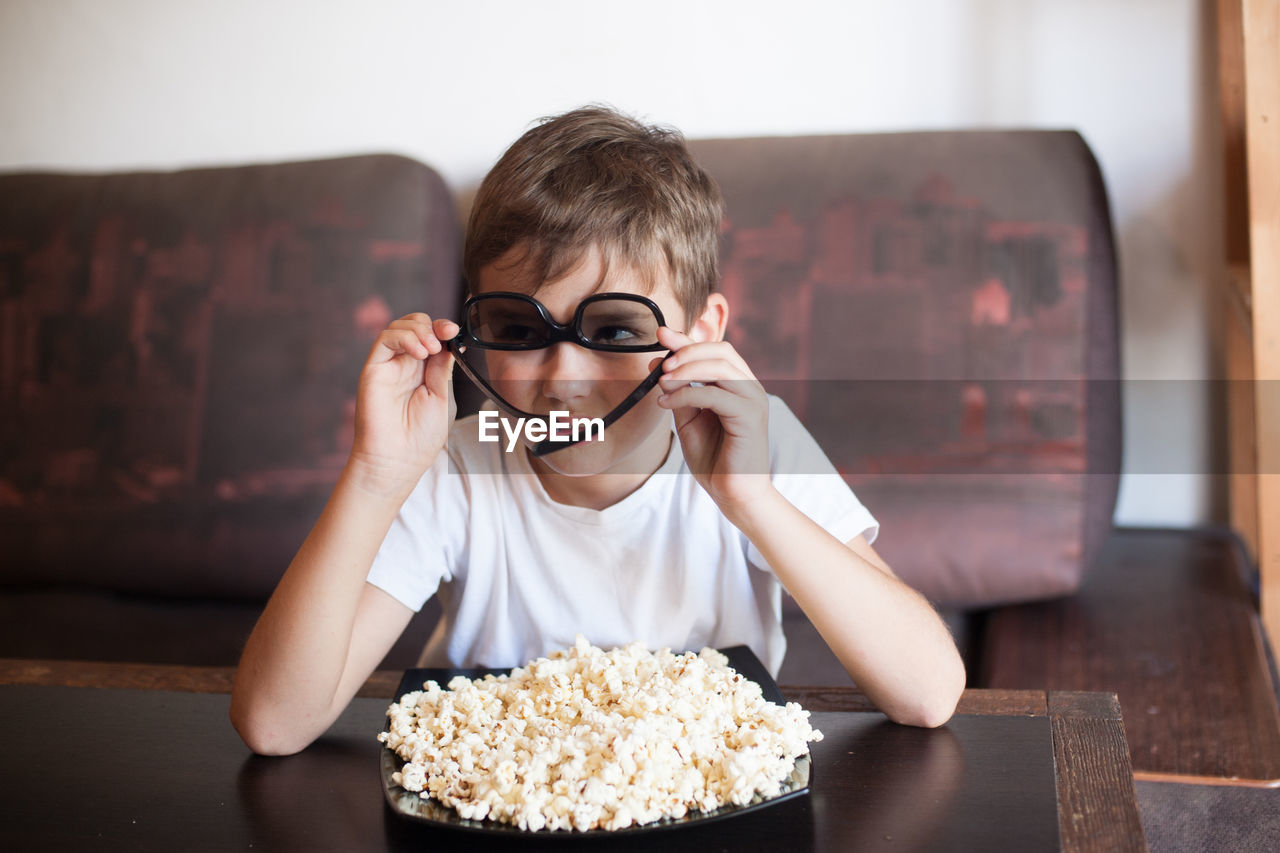 A boy in 3d glasses watches a movie and eats popcorn with his mouth wide open sitting on the couch
