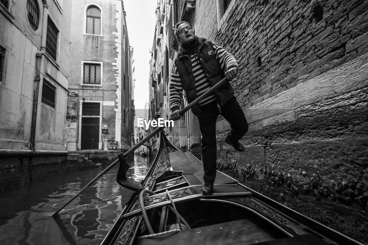 architecture, built structure, building exterior, one person, real people, full length, transportation, day, outdoors, men, gondola - traditional boat, city, adult, people