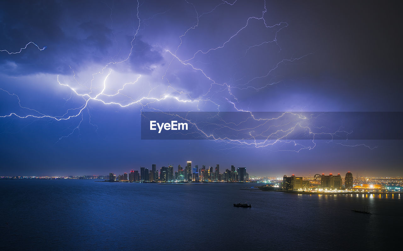 Lightning Over Illuminated City By Sea At Night