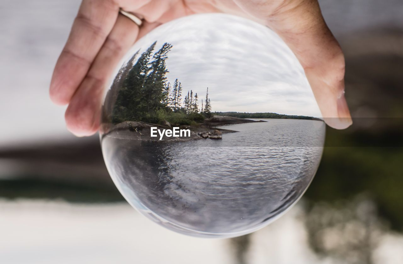Cropped Image Of Hand Holding Crystal Ball Against Lake
