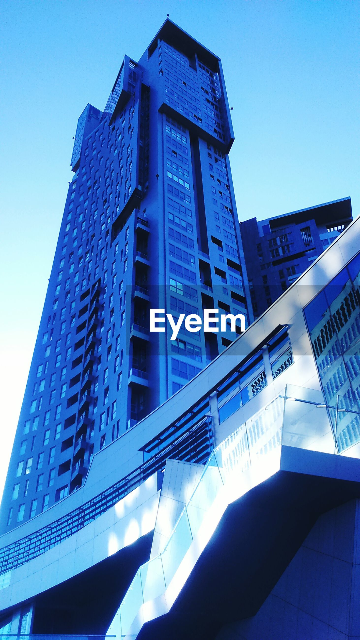building exterior, architecture, low angle view, built structure, clear sky, office building, modern, city, skyscraper, tall - high, building, blue, tower, sunlight, day, tall, outdoors, sky, reflection, city life