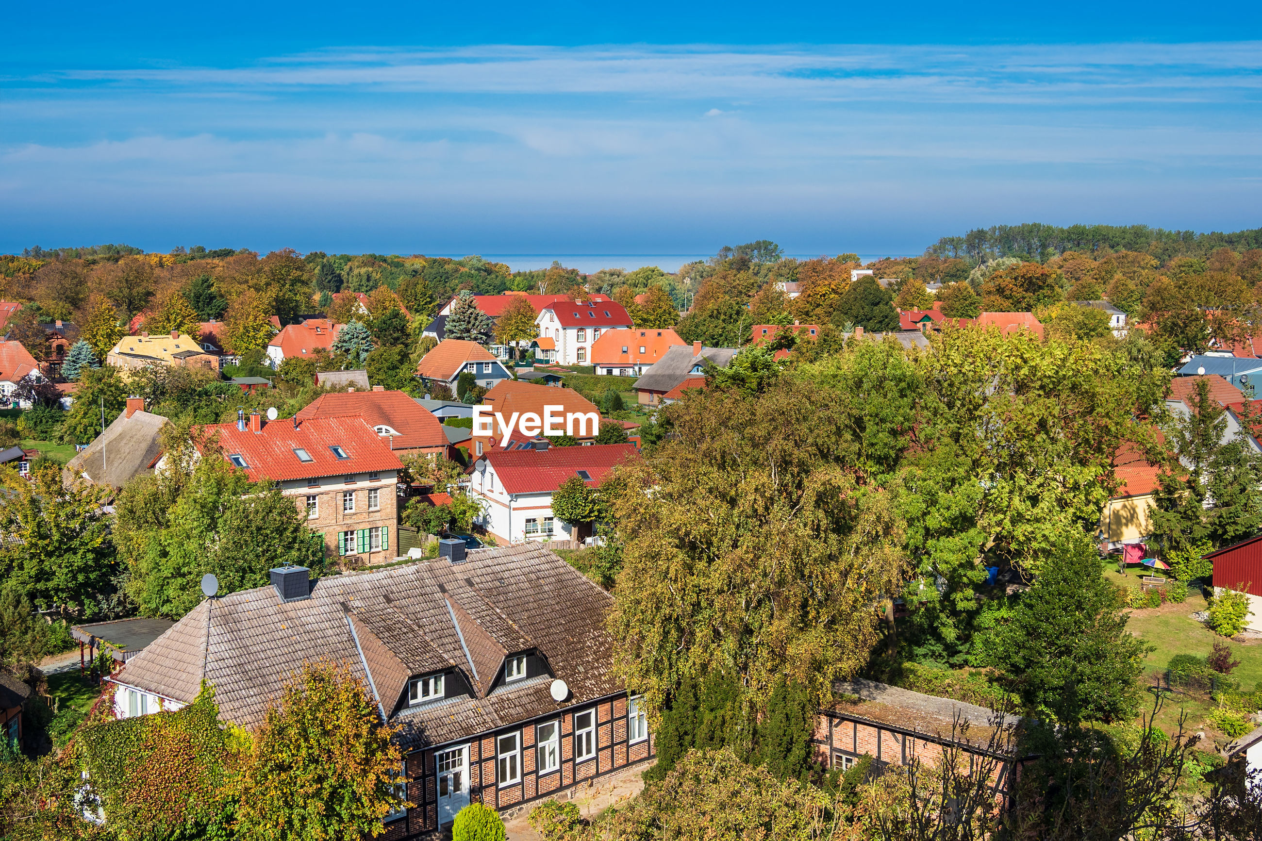 HIGH ANGLE VIEW OF TOWNSCAPE AND TREES BY HOUSES AGAINST SKY