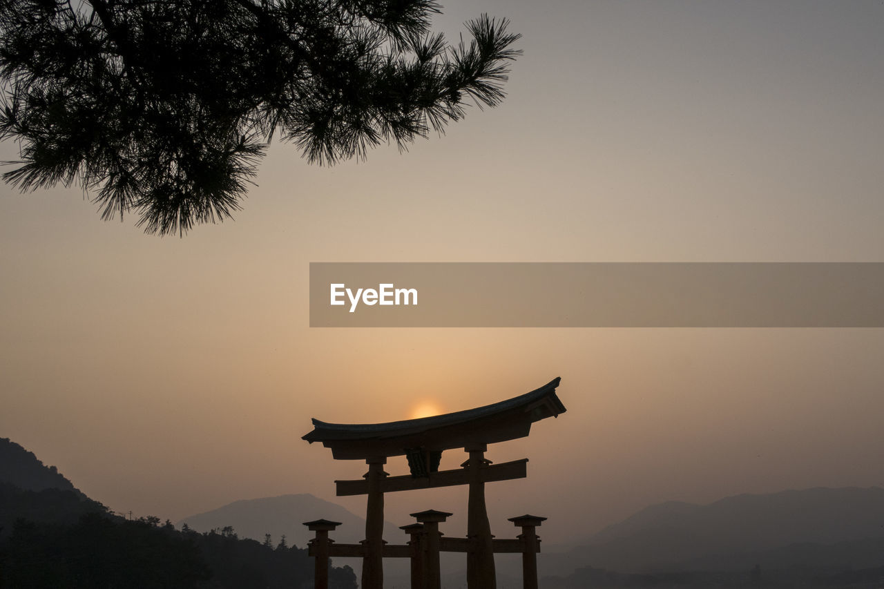 sunset, sky, religion, belief, silhouette, spirituality, orange color, nature, tree, beauty in nature, mountain, tranquility, plant, tranquil scene, no people, place of worship, scenics - nature, non-urban scene, travel destinations, outdoors, shrine