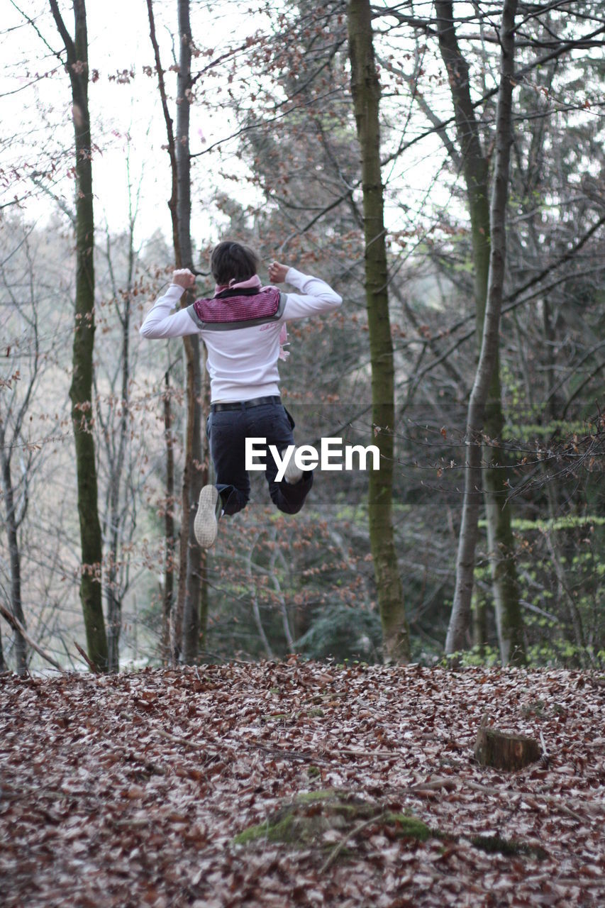 Rear view full length of playful man jumping in forest