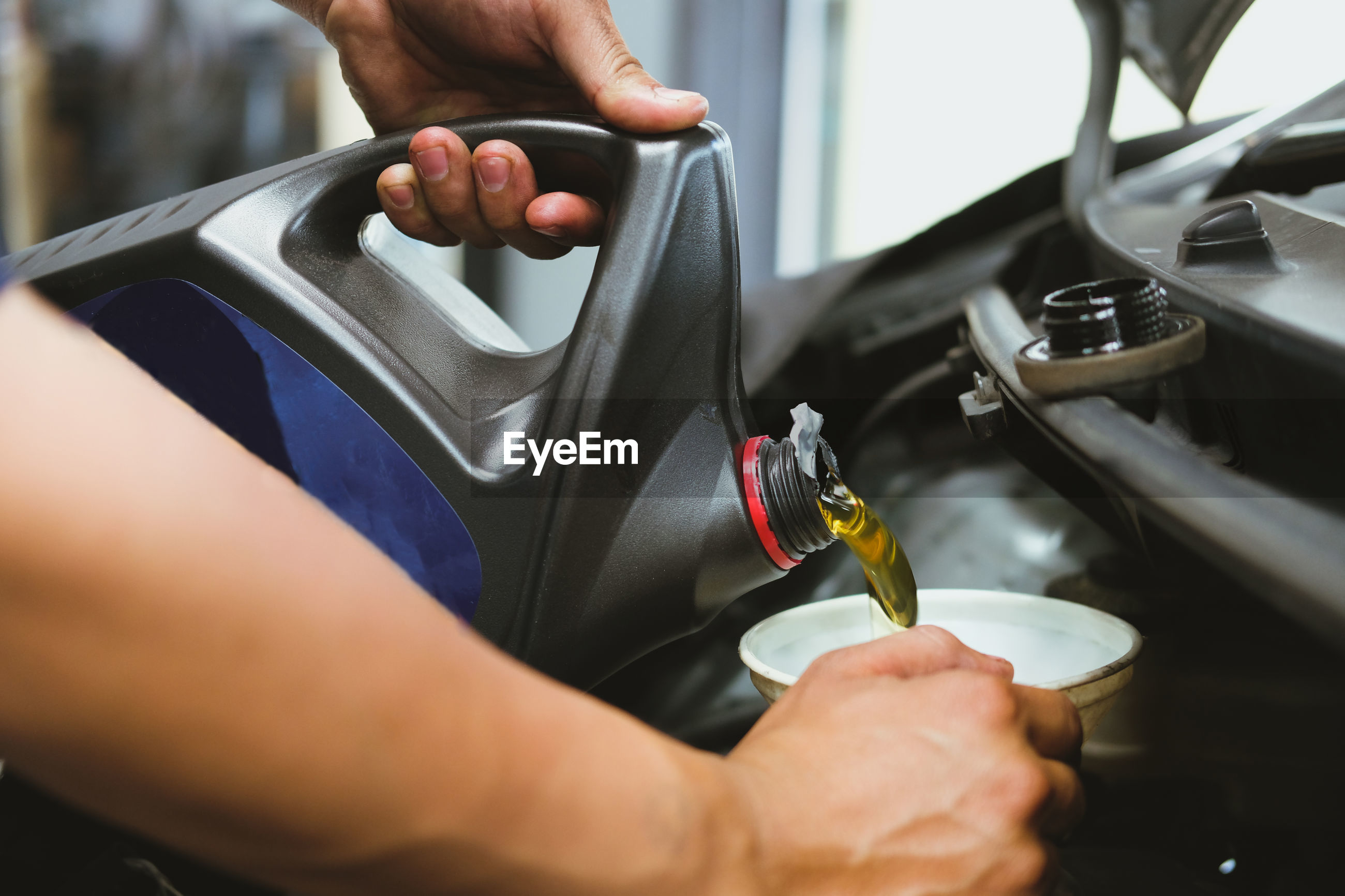 Cropped hand pouring oil in vehicle engine
