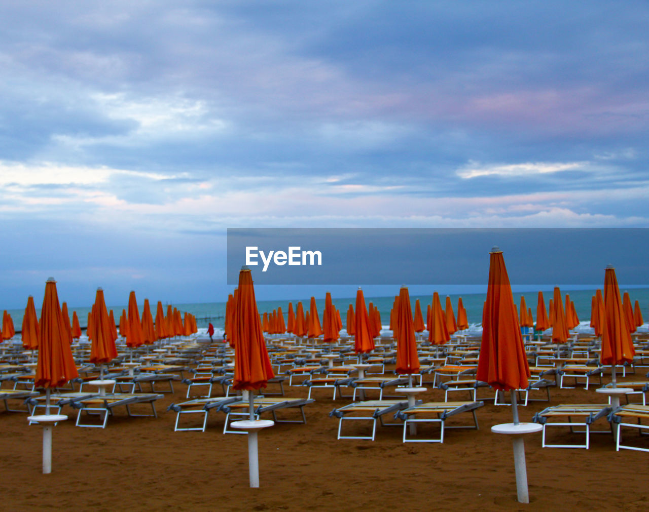 sky, chair, cloud - sky, in a row, land, seat, beach, nature, no people, lounge chair, absence, large group of objects, tranquility, sand, beauty in nature, closed, parasol, shade, scenics - nature, day, outdoors, order