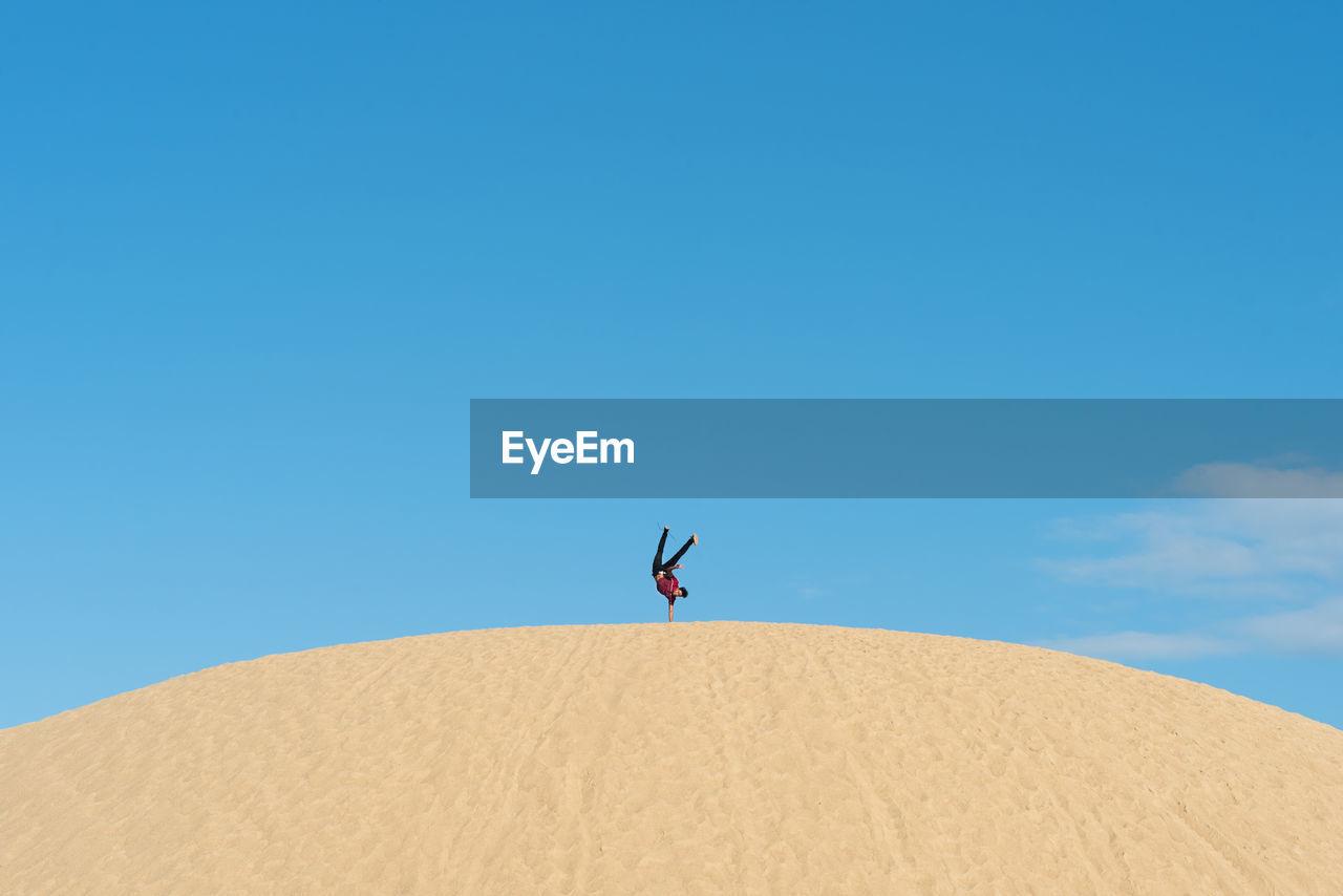 Man doing handstand at desert against clear blue sky