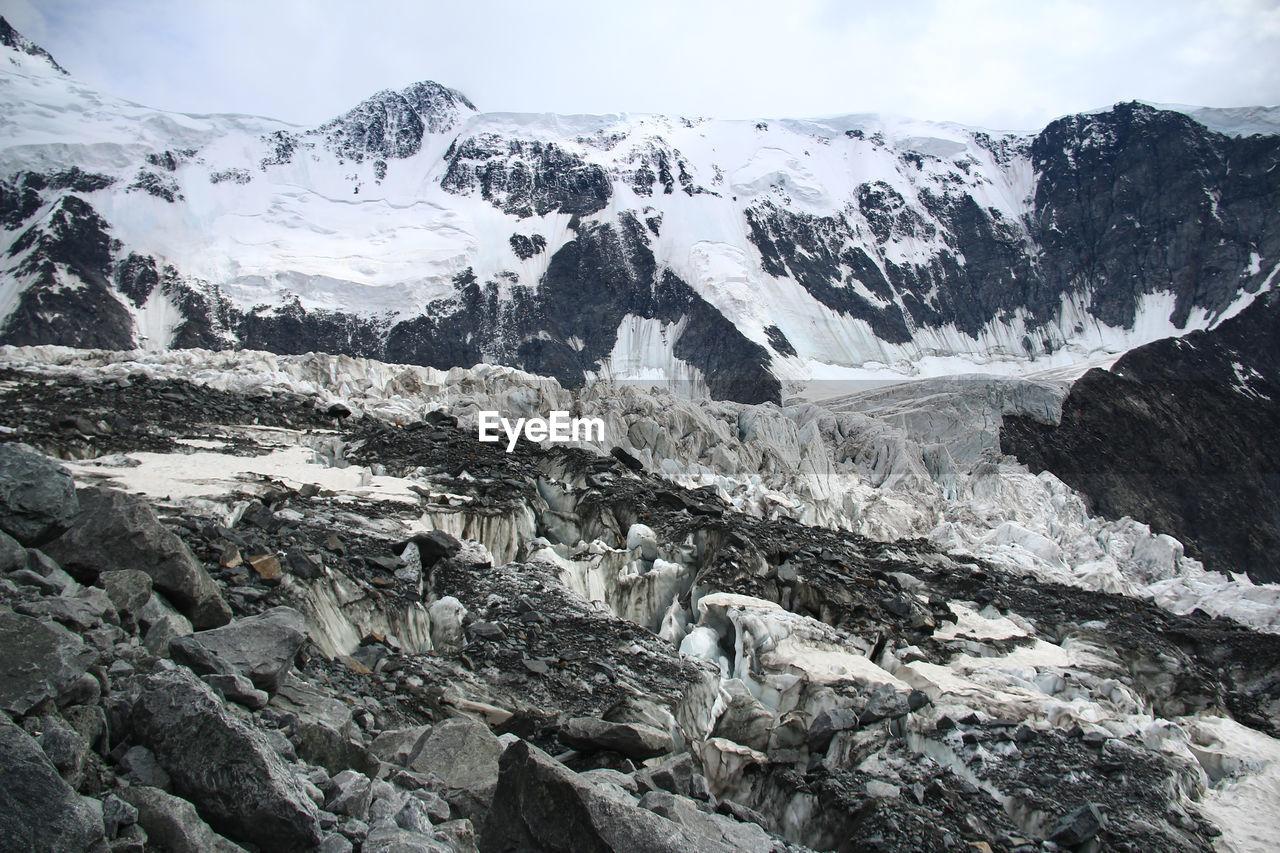 Alpine glacier on mount belukha, rocks, snow and stones