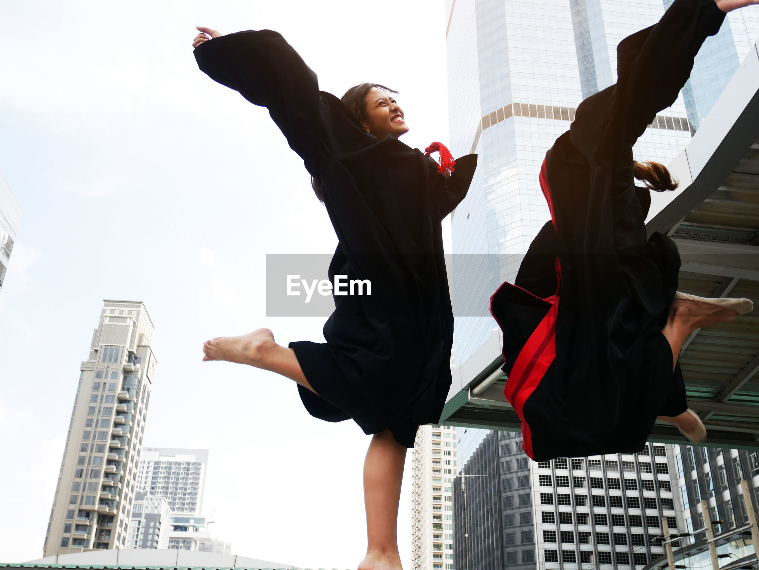 Low angle view of happy friends jumping against buildings in city