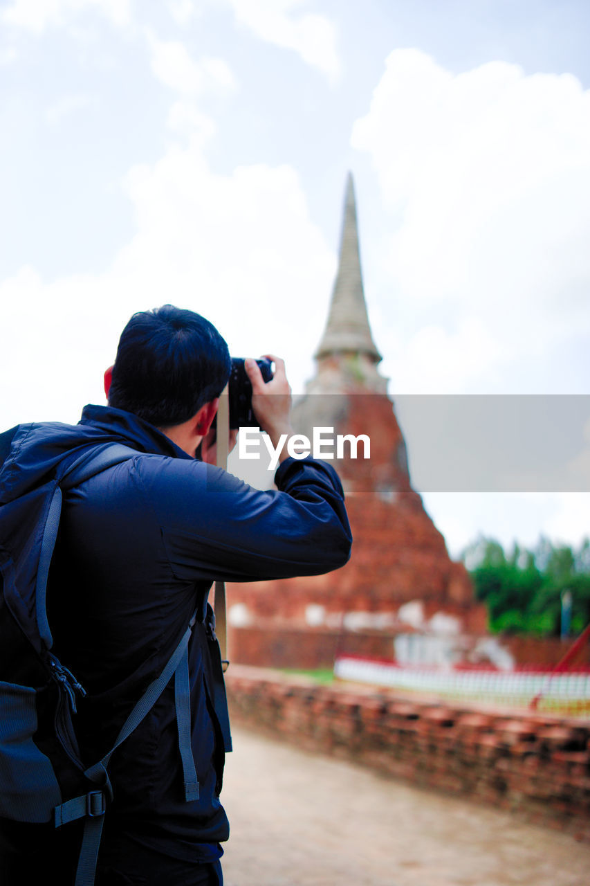 Man photographing stupa against sky