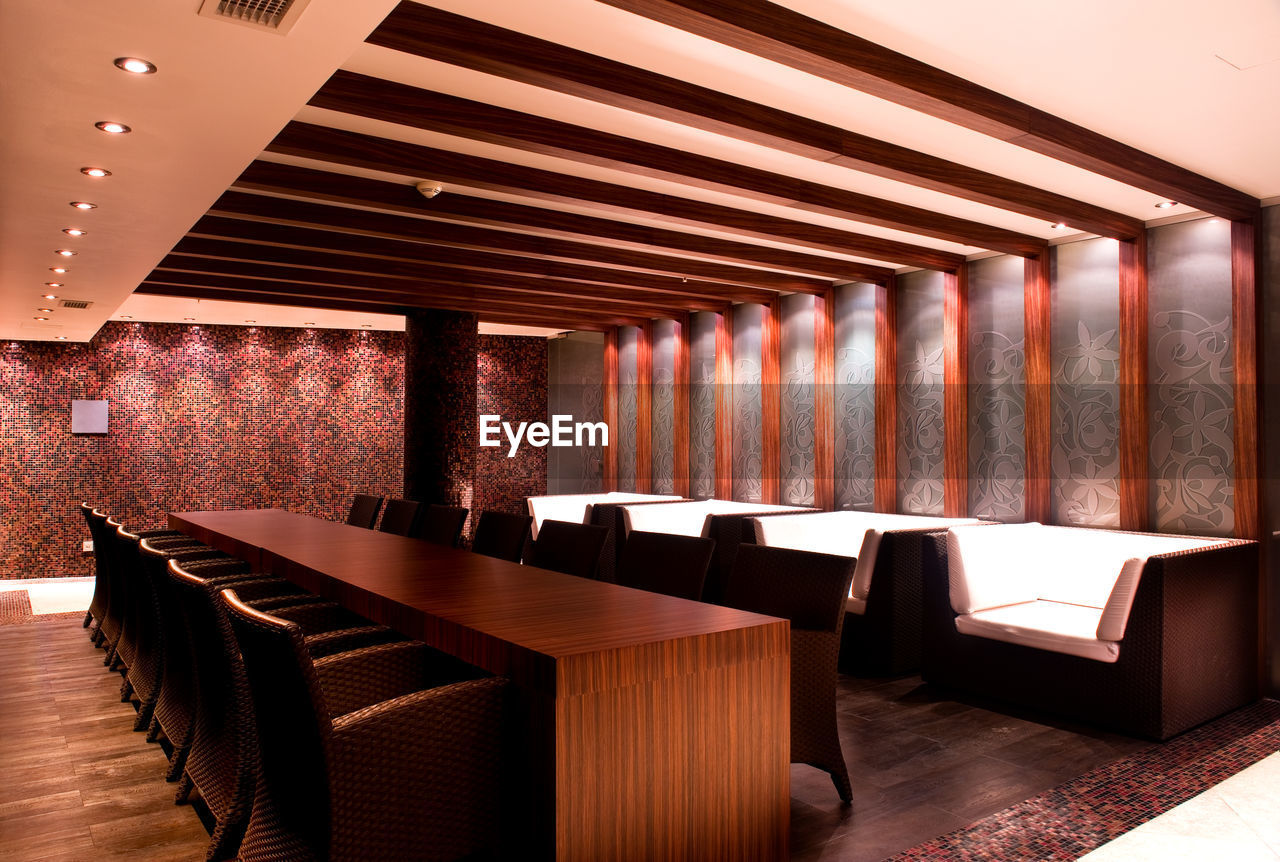 indoors, no people, architecture, empty, seat, absence, built structure, chair, flooring, table, luxury, arrangement, pattern, furniture, business, wealth, wood - material, in a row, restaurant, decoration, ceiling, architectural column