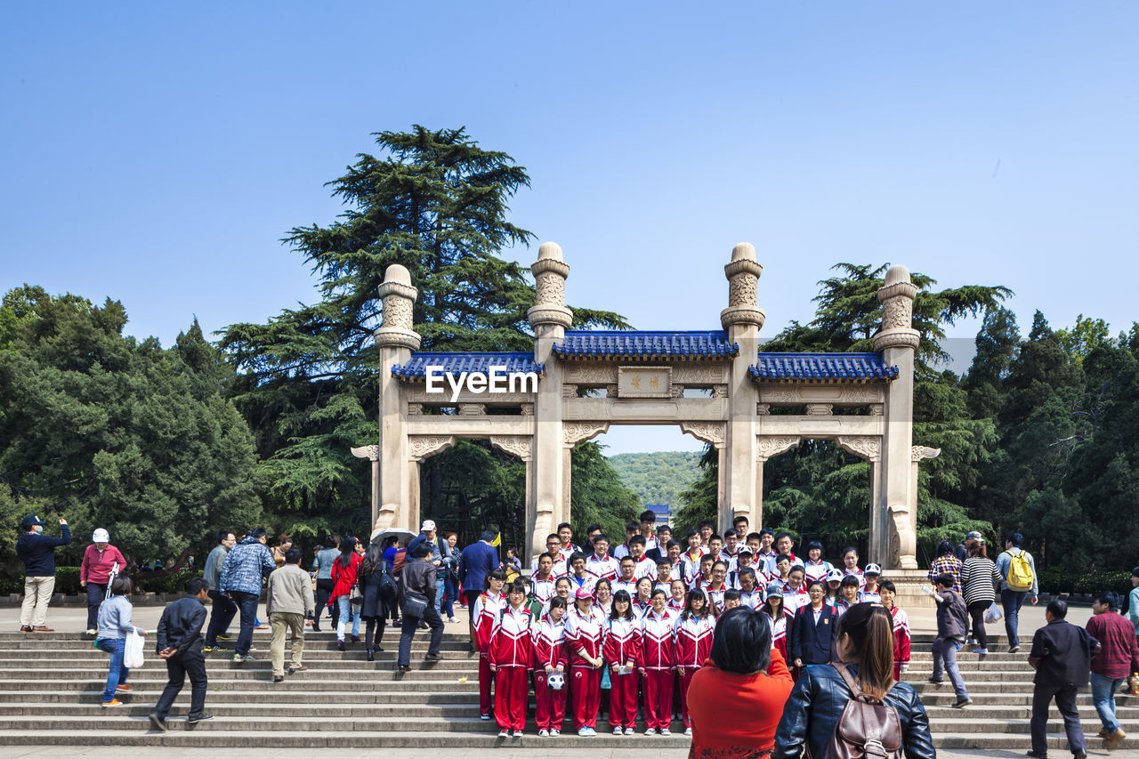 large group of people, tree, clear sky, real people, day, architecture, building exterior, built structure, travel destinations, outdoors, blue, sky, crowd, men, women, nature, people
