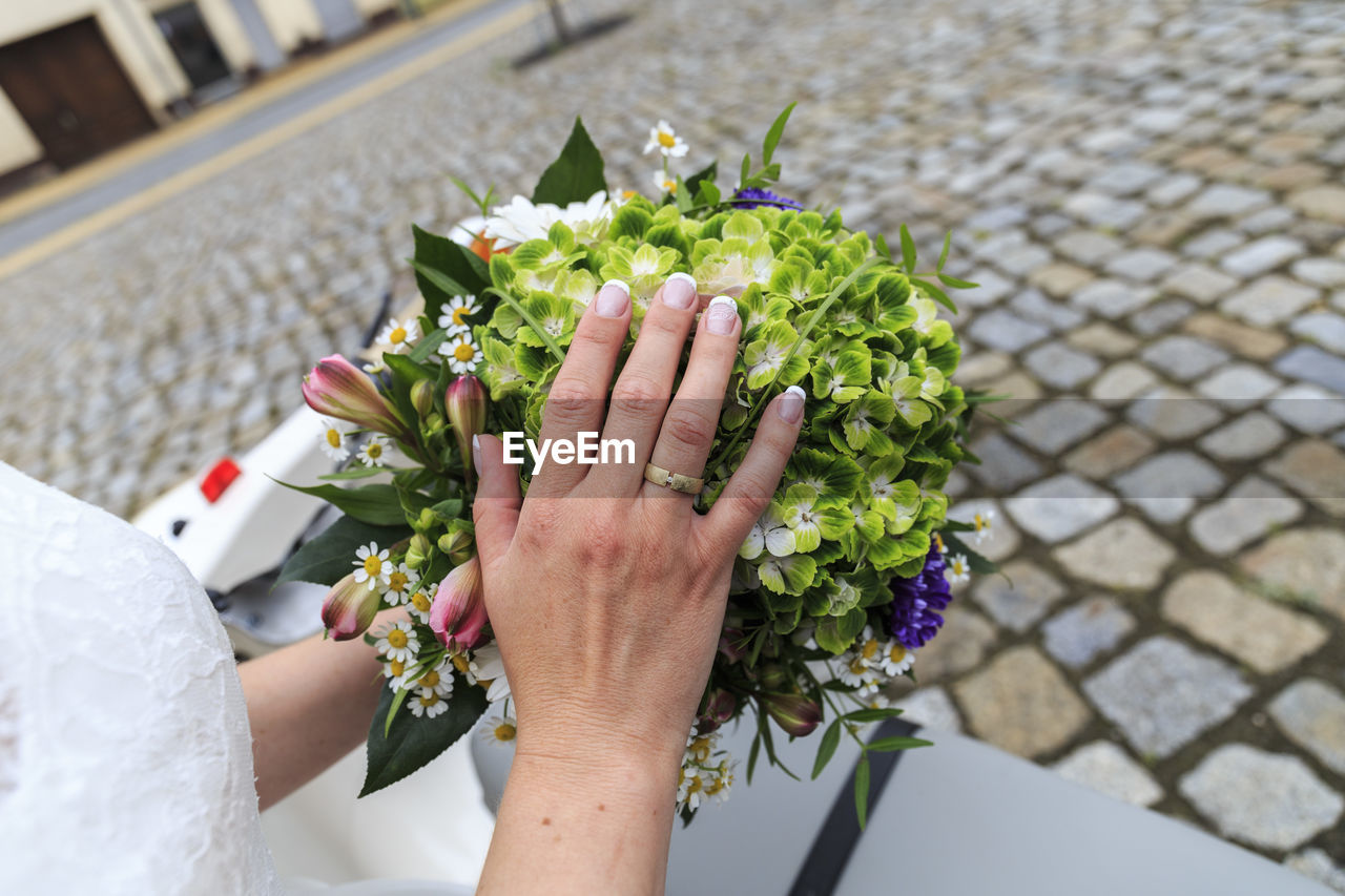 Cropped image of bride holding bouquet