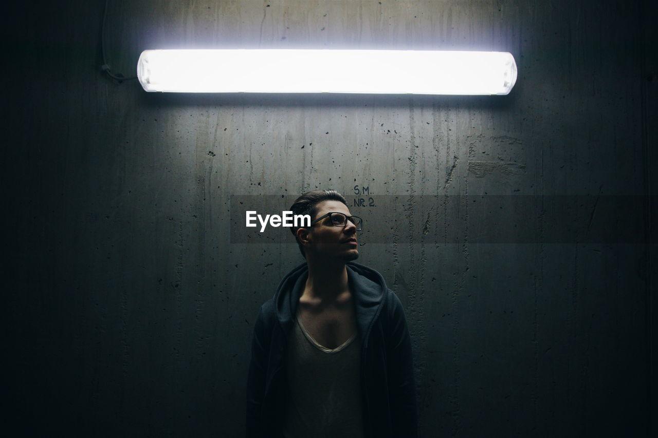 Man Standing Below Fluorescent Light Against Wall