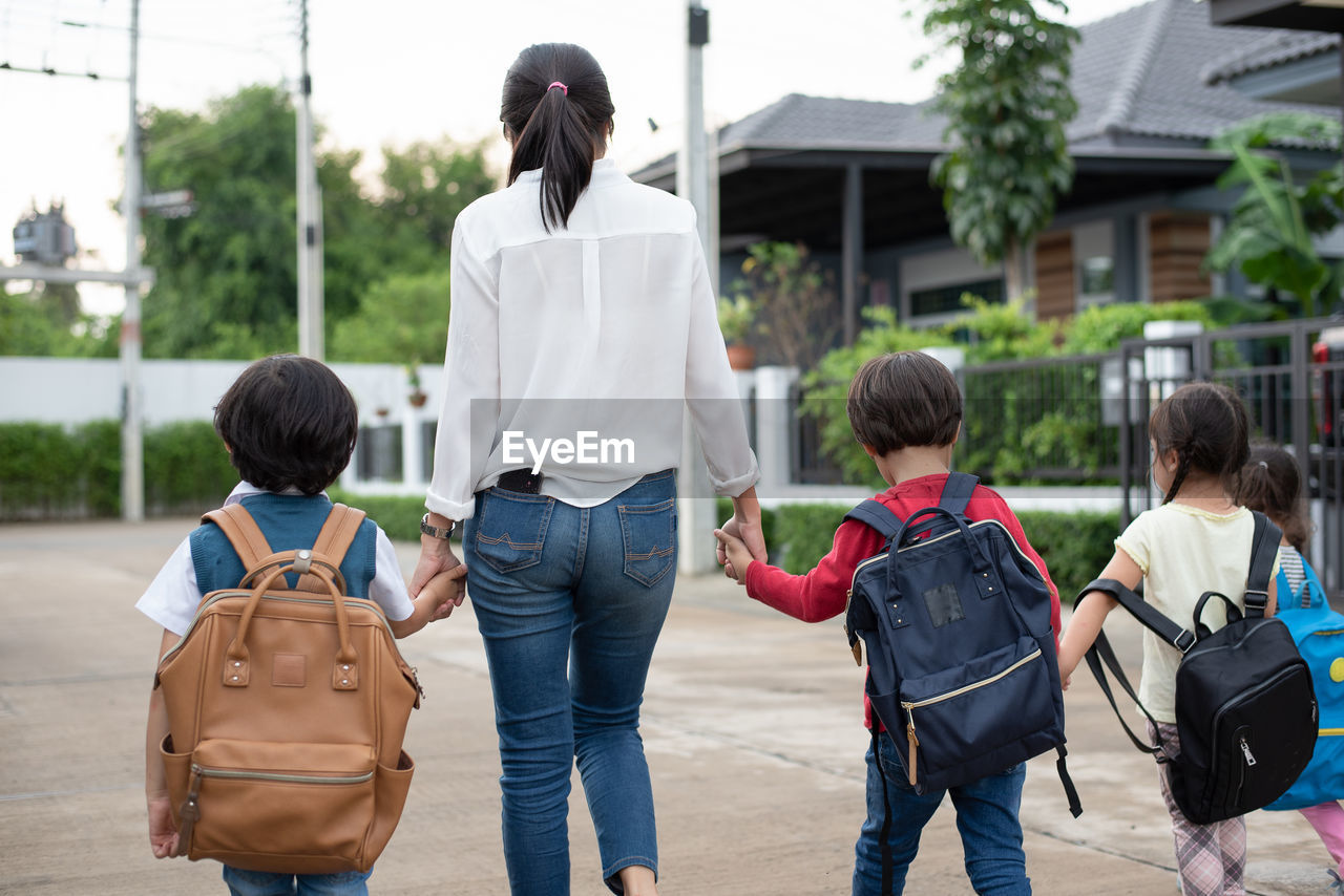 Rear view of mother with children walking on footpath