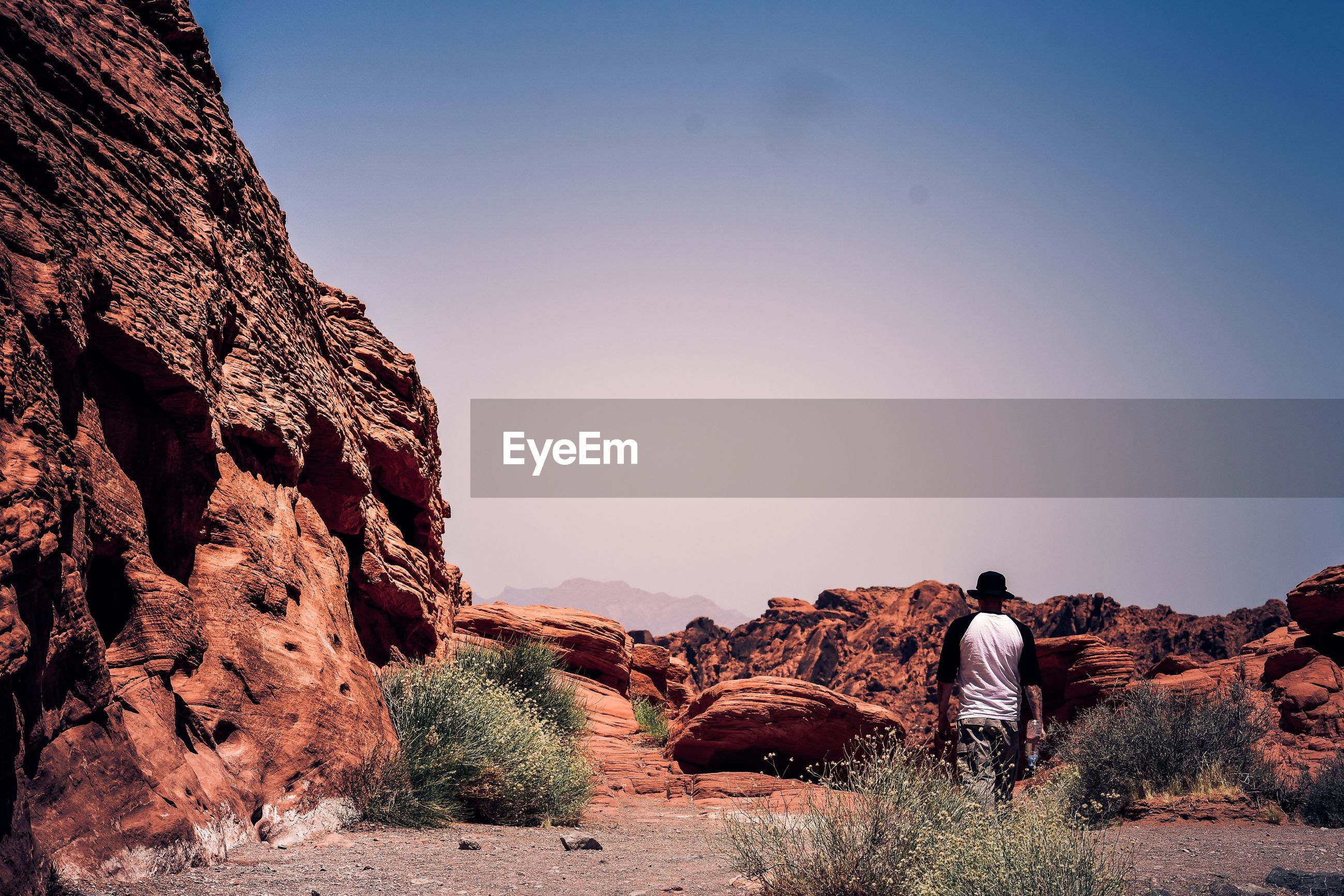 Rear view of man walking against rock formations