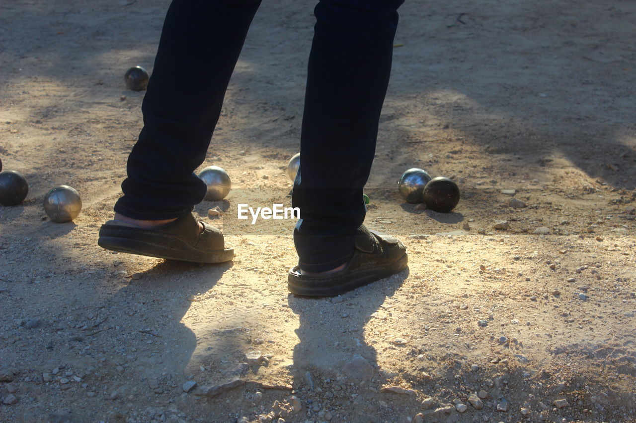 Low section of person standing on field by metal balls