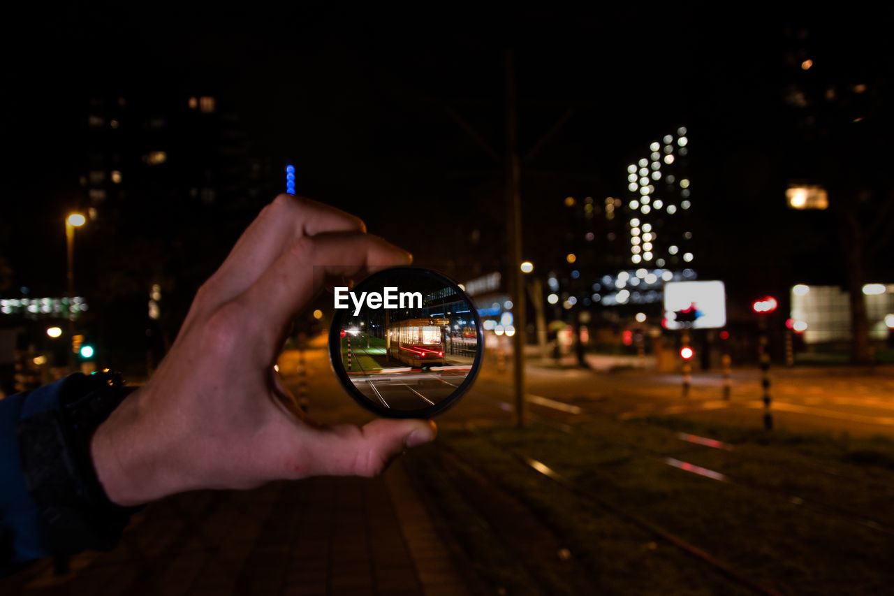 human hand, hand, night, city, illuminated, architecture, human body part, building exterior, one person, built structure, holding, real people, focus on foreground, communication, finger, technology, human finger, lifestyles, city life, wireless technology, outdoors, cityscape