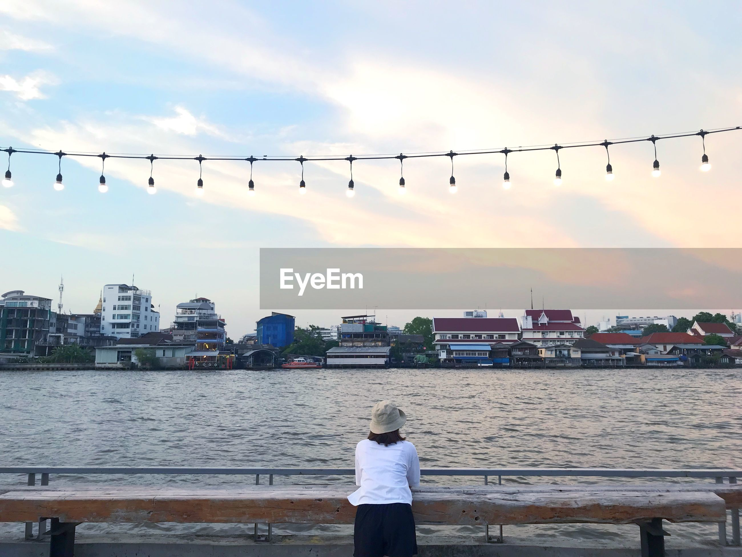 Rear view of woman looking at river against sky in city