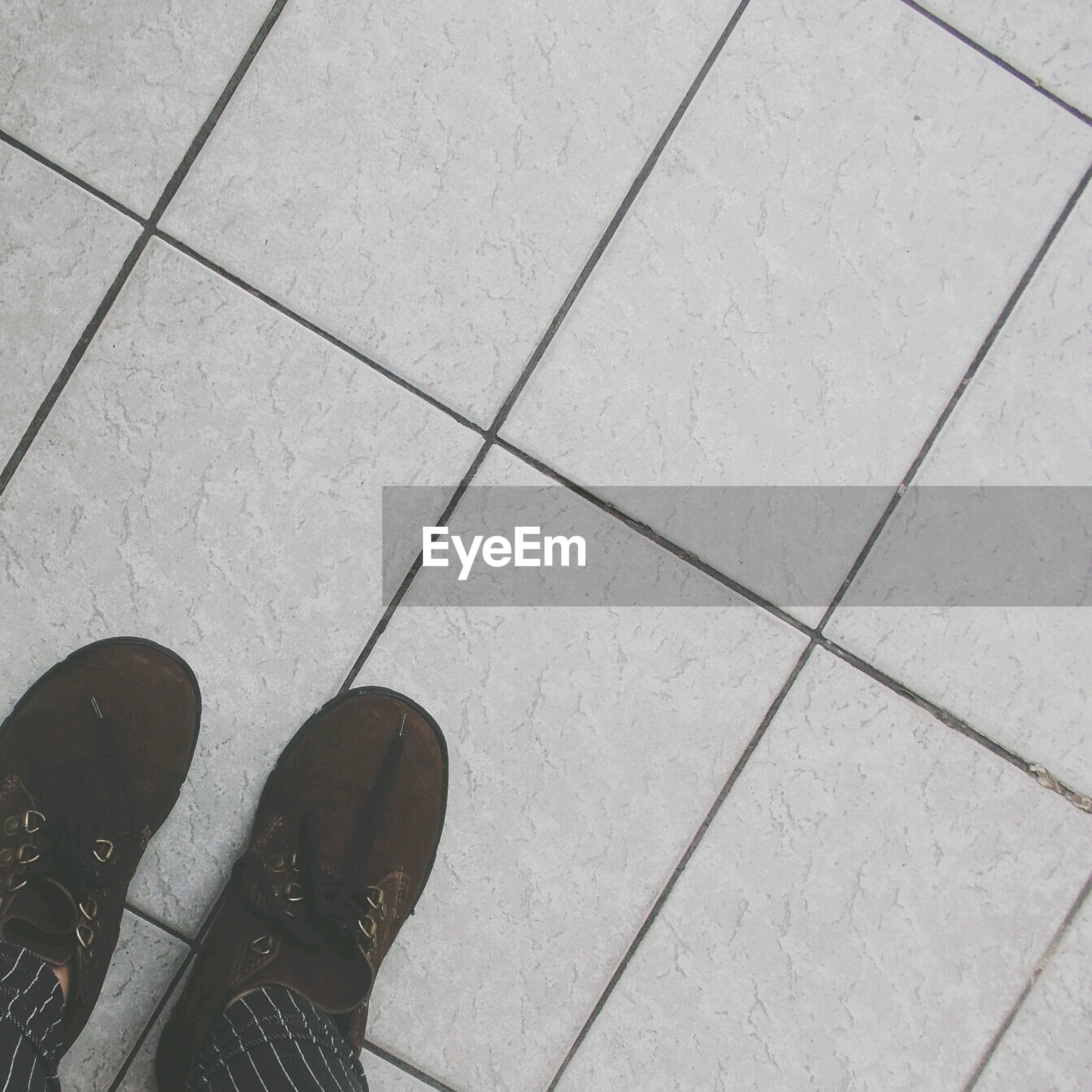 high angle view, tiled floor, flooring, pattern, indoors, tile, paving stone, geometric shape, floor, shadow, shoe, design, directly above, day, sunlight, low section, footpath, elevated view, full frame, square shape