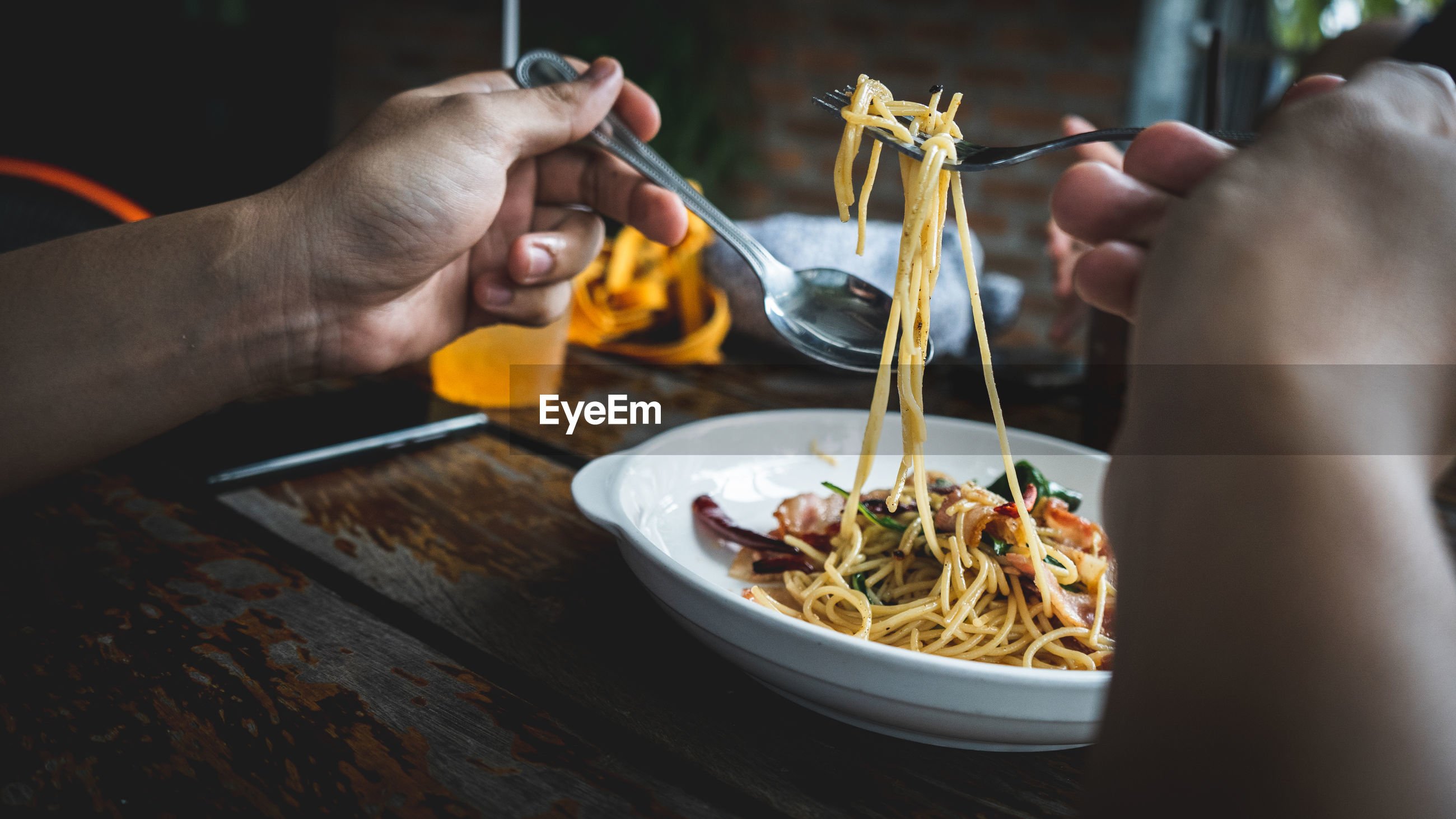 Midsection of person eating noodles on table