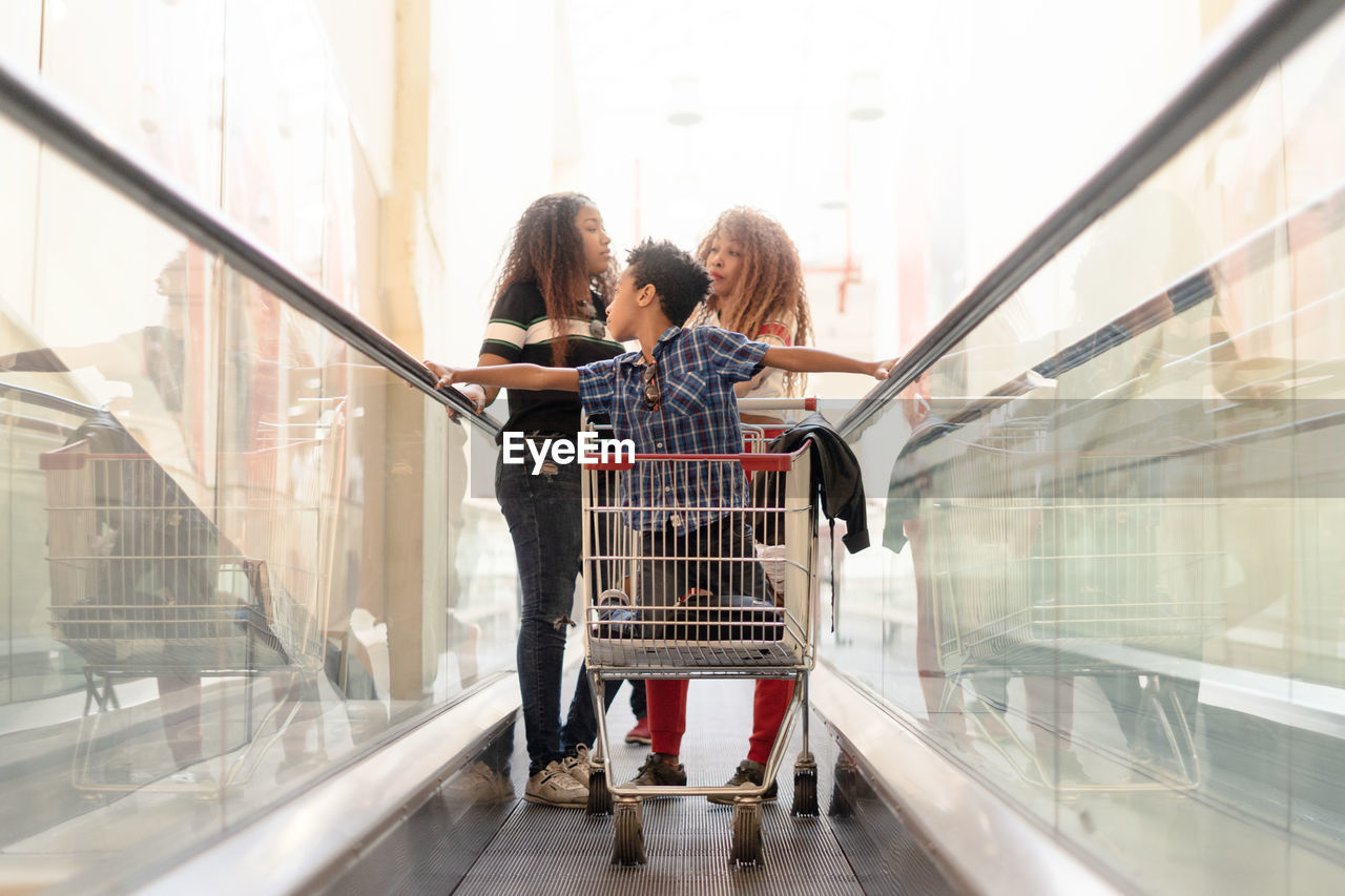 Boy In Shopping Cart With Family Over Escalator