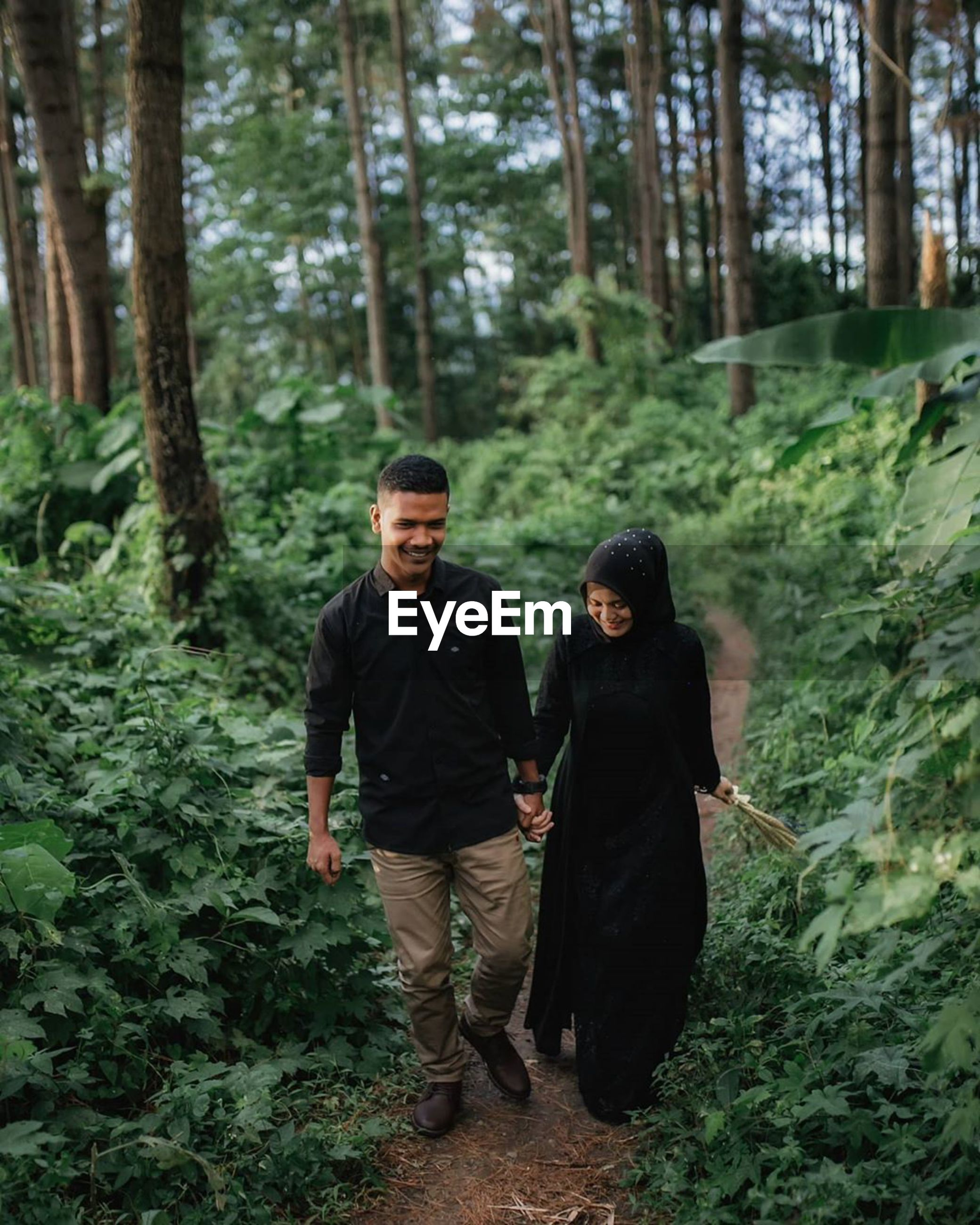 YOUNG COUPLE WALKING ON A FOREST