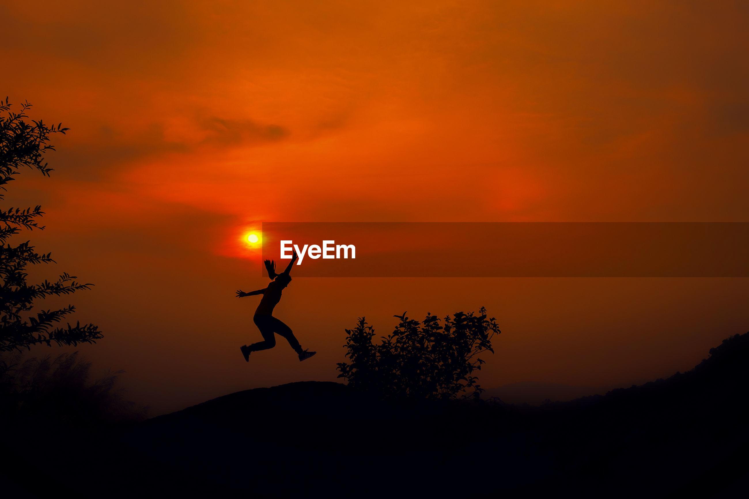 Silhouette man jumping on field against orange sky