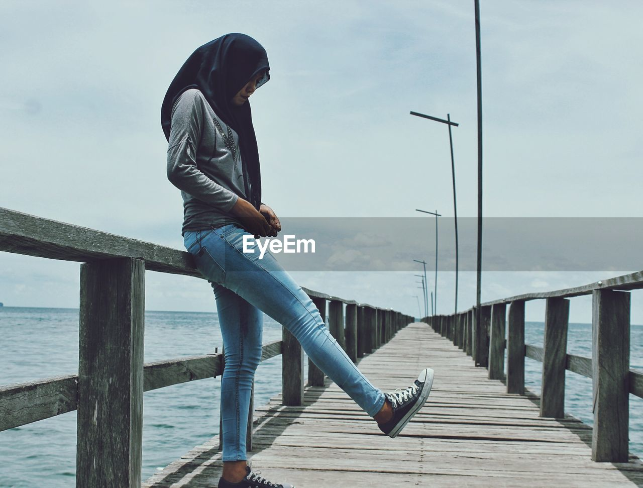 Woman Standing On Wooden Pier