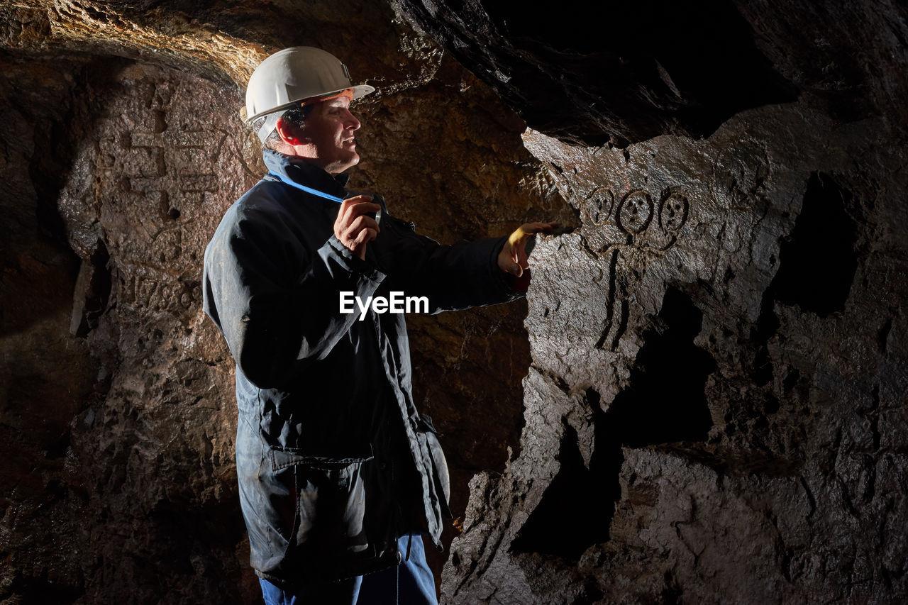 Man Wearing Helmet Standing In Cave