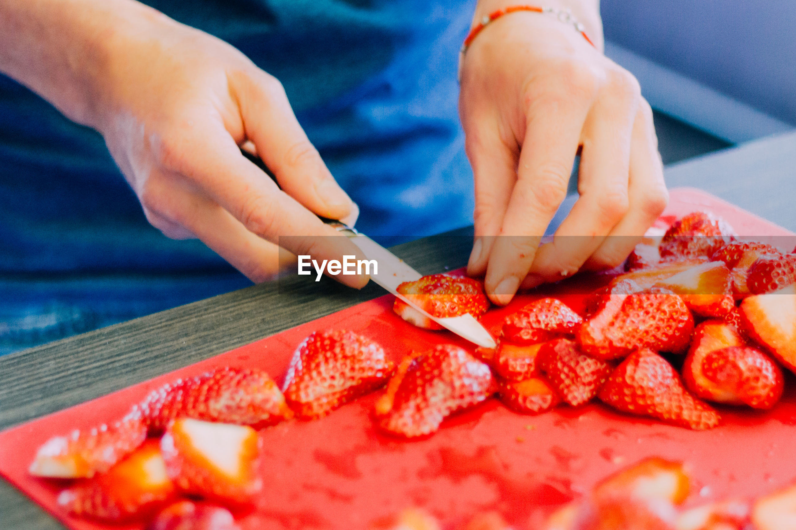 Close-up of hand slicing strawberries
