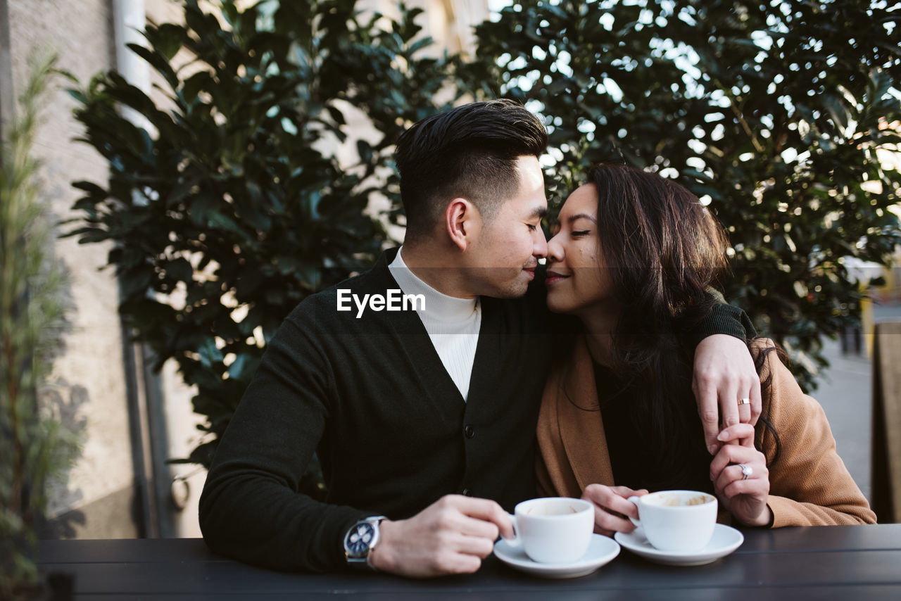 YOUNG COUPLE HOLDING COFFEE CUP