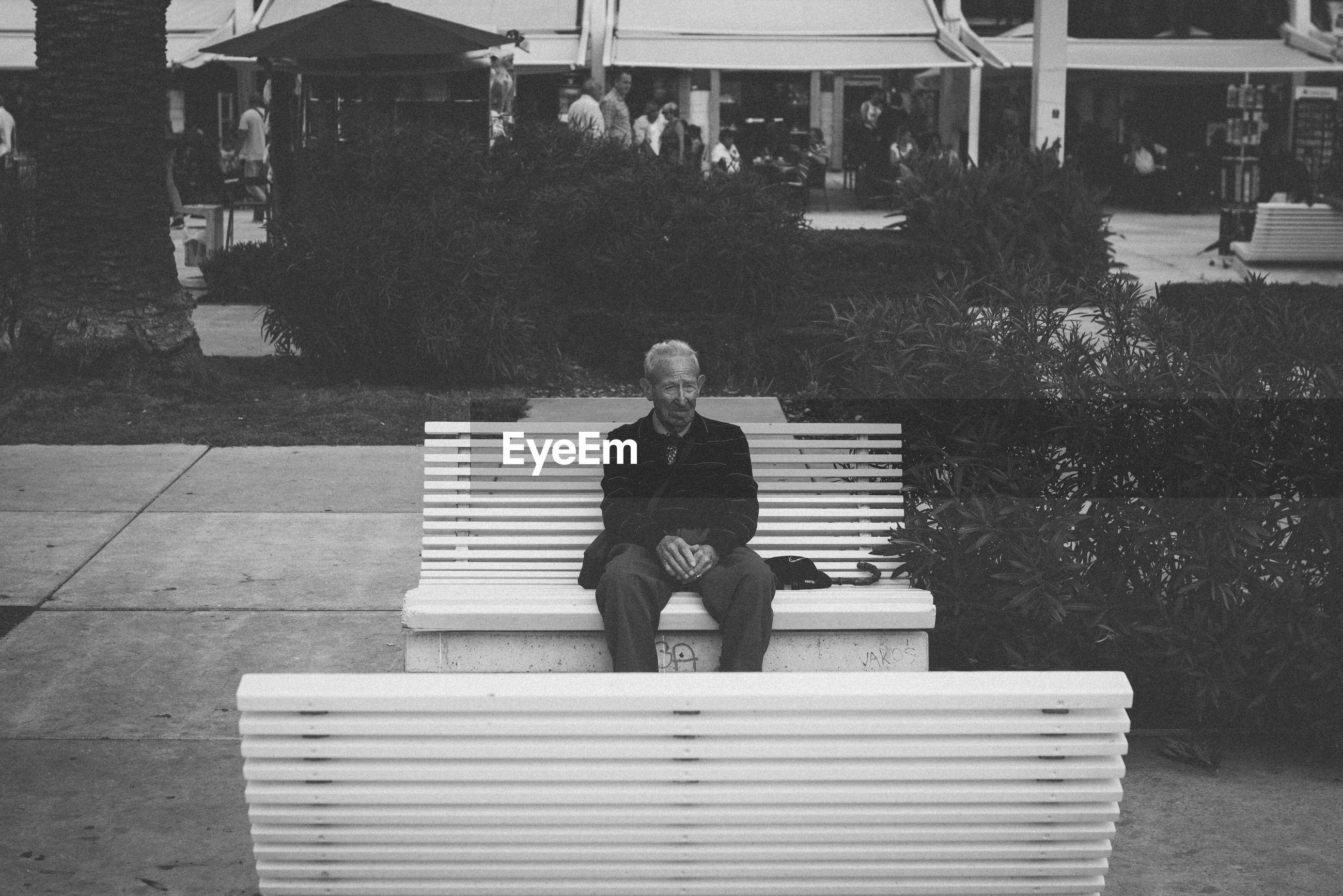 FULL LENGTH OF MAN SITTING ON COBBLESTONE