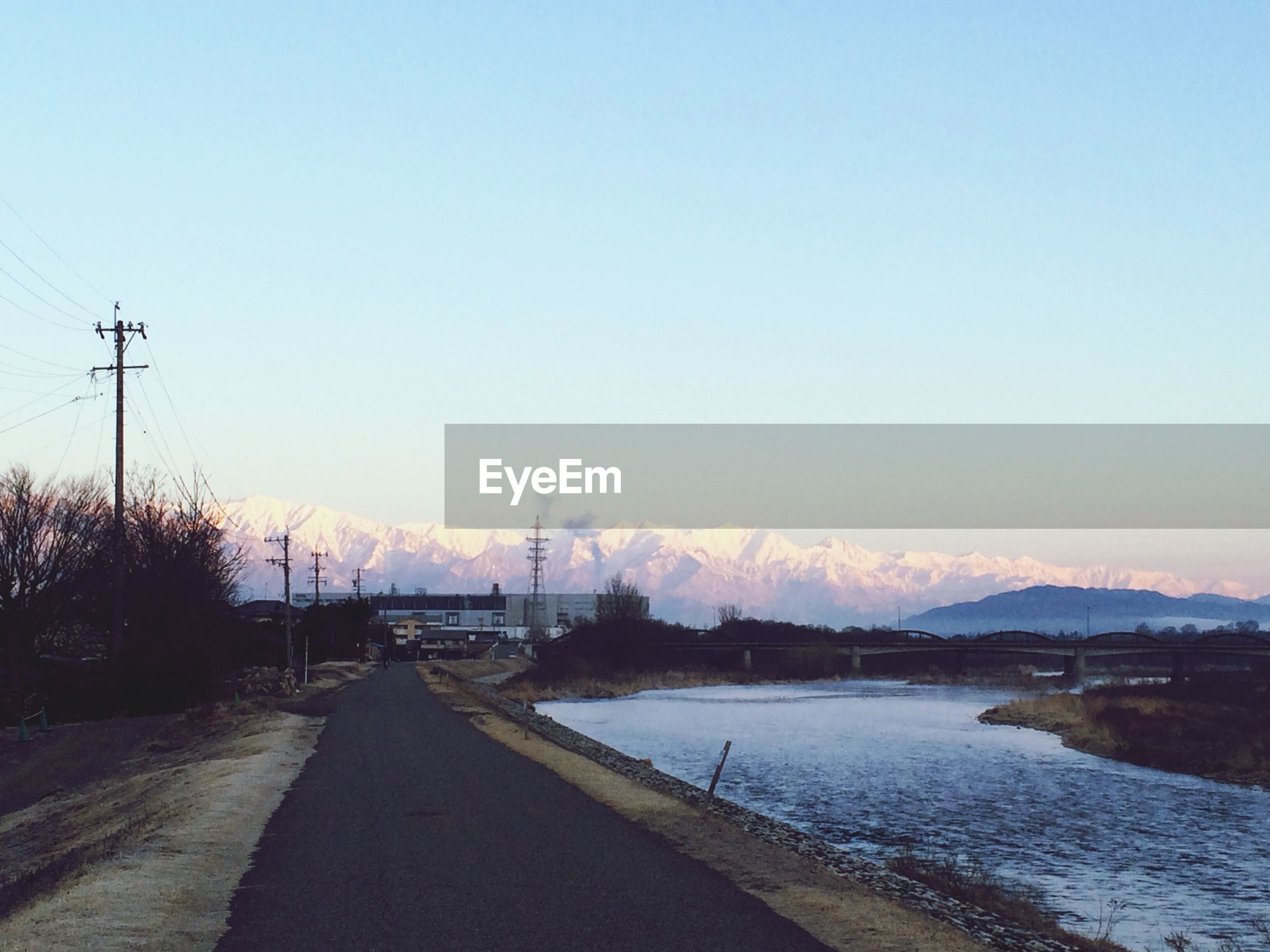 clear sky, copy space, road, transportation, tranquility, the way forward, tranquil scene, water, landscape, electricity pylon, nature, scenics, beauty in nature, mountain, outdoors, sunset, no people, winter, diminishing perspective, street