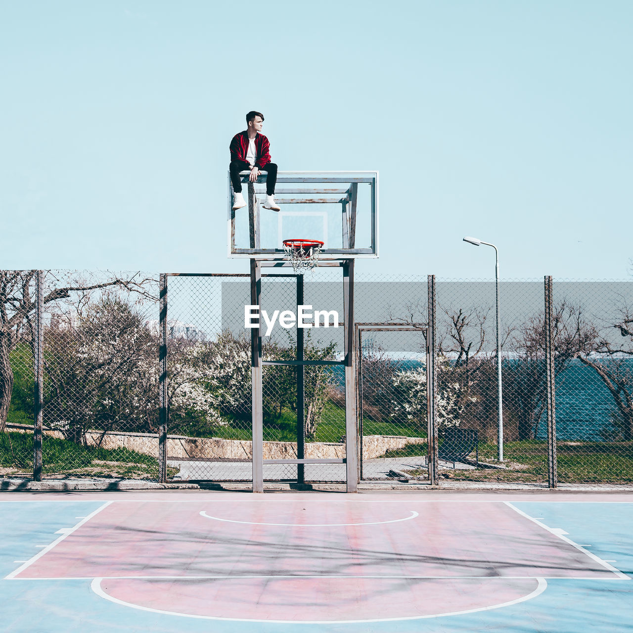 Man Sitting On Basketball Hoop Against Sky