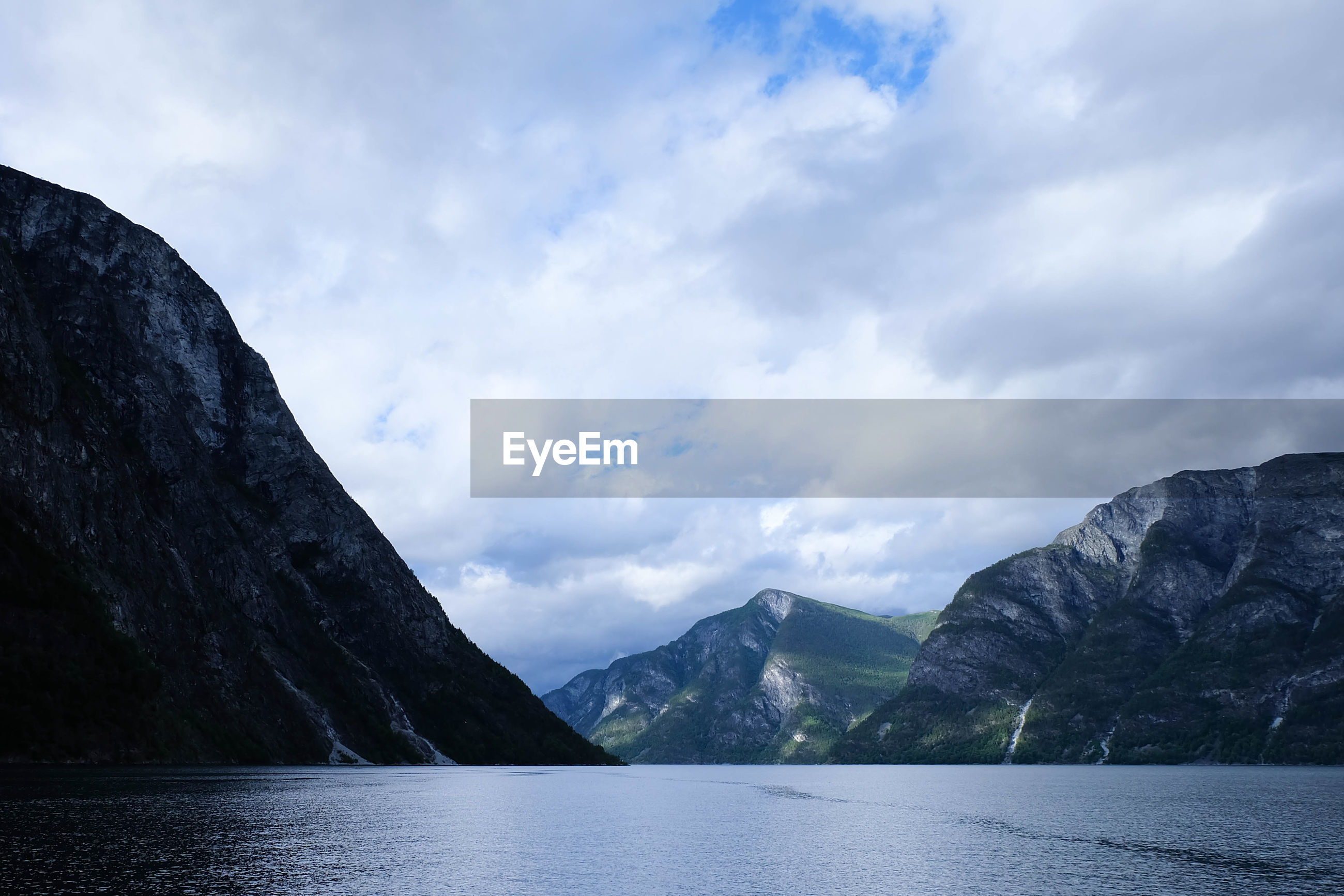 Scenic view of lake and mountains against cloudy sky
