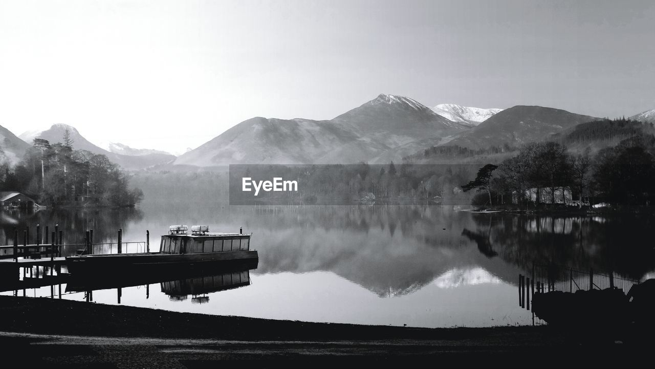 View Of Boats In Calm Lake Against Mountain Range
